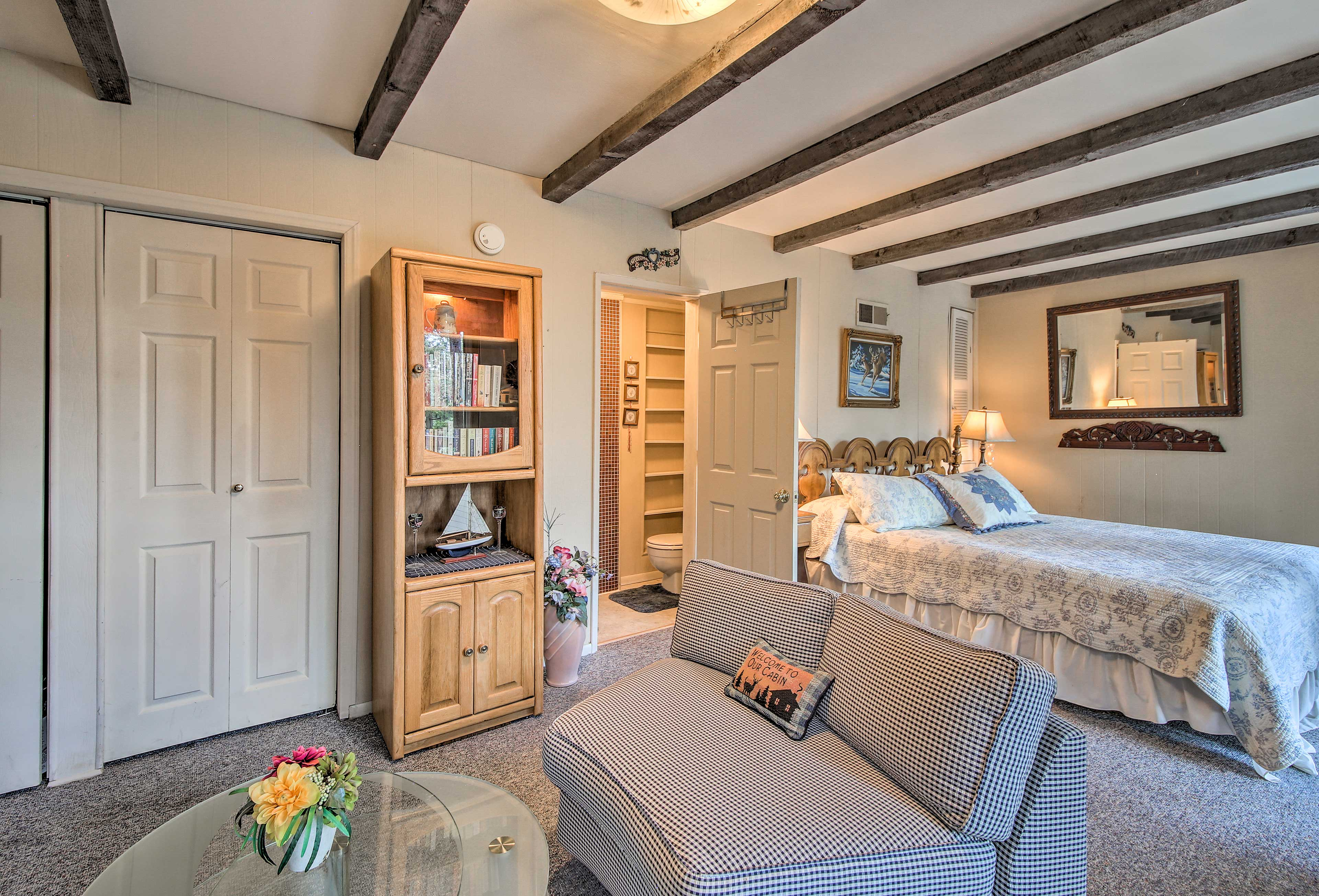 The room features a sitting area, king bed, deck access and en-suite bath.
