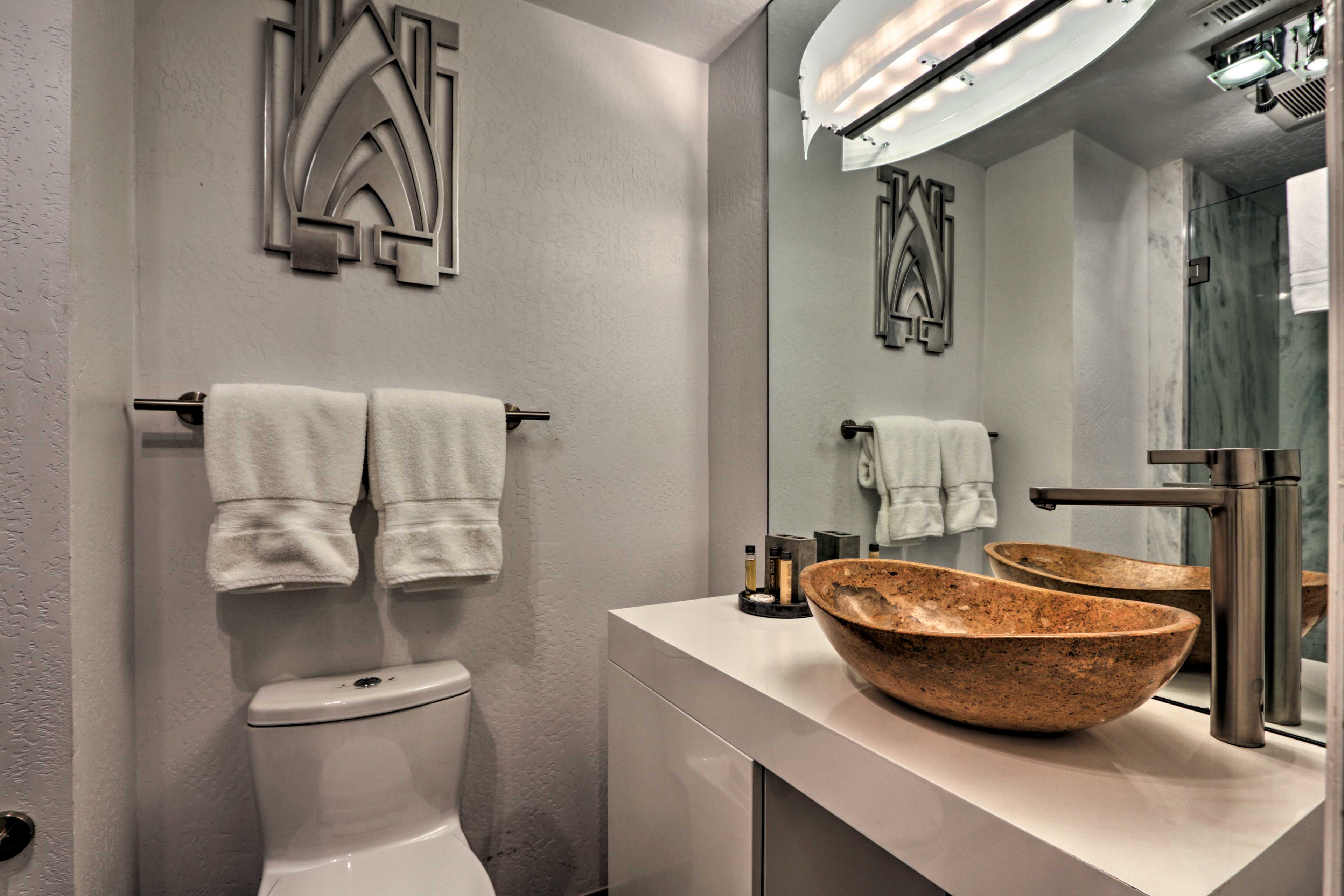 The en-suite bath boasts a stylish bowl sink and walk-in shower.