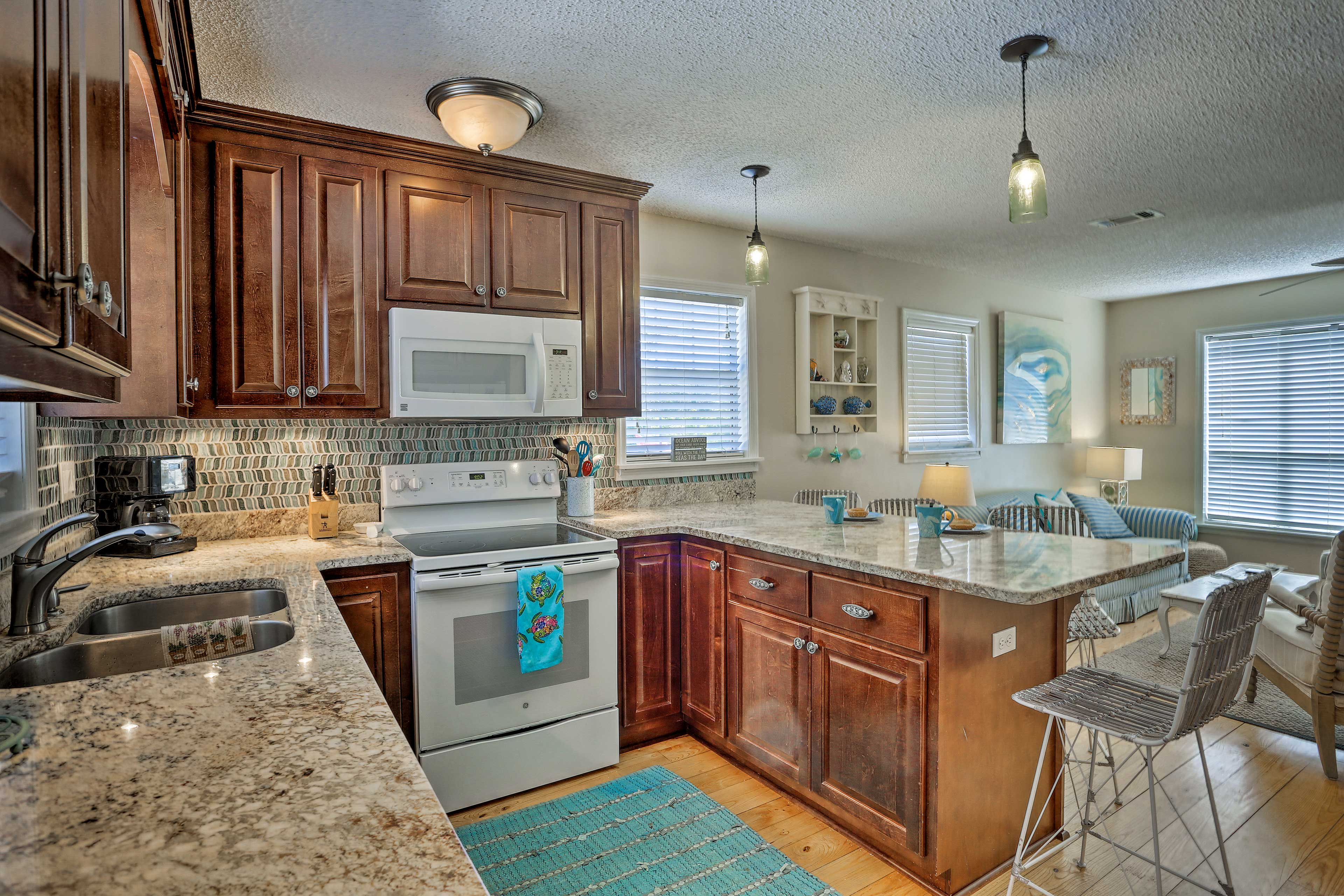 The fully equipped kitchen offers granite countertops.