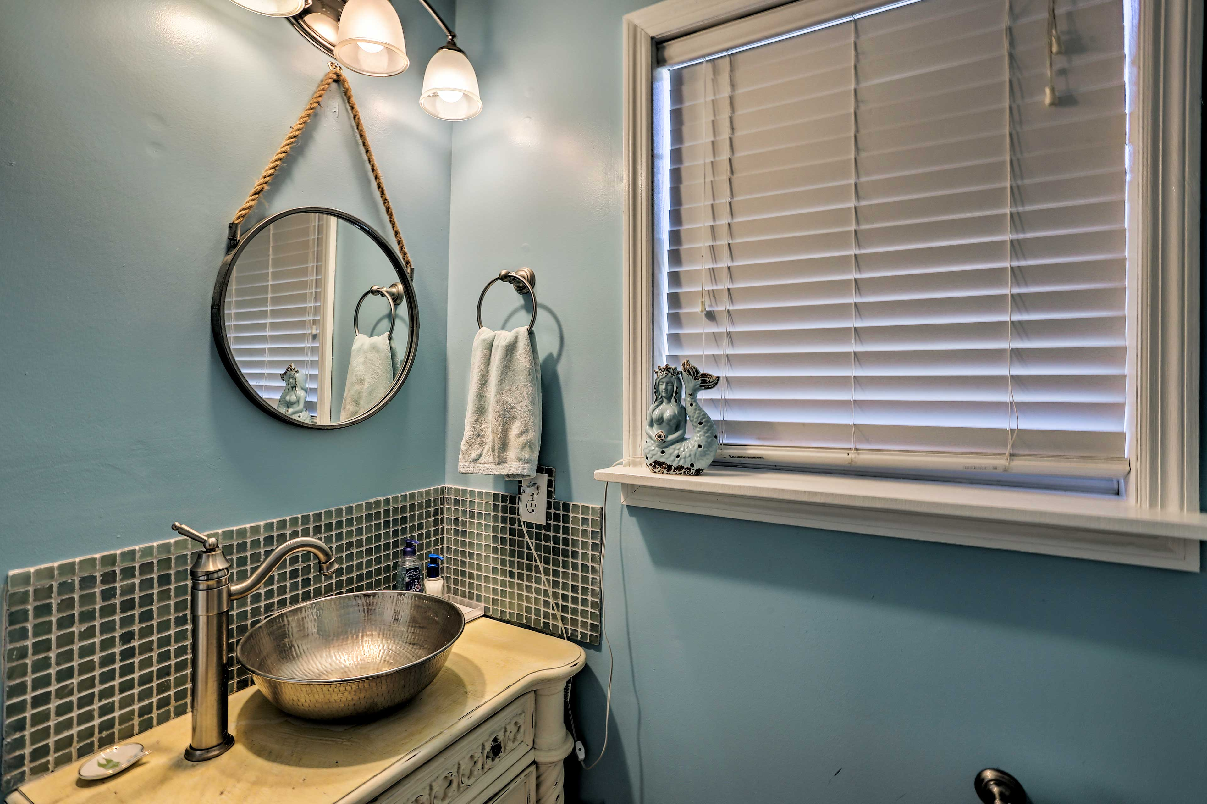 This chic bathroom features a vessel sink and nautical decor.