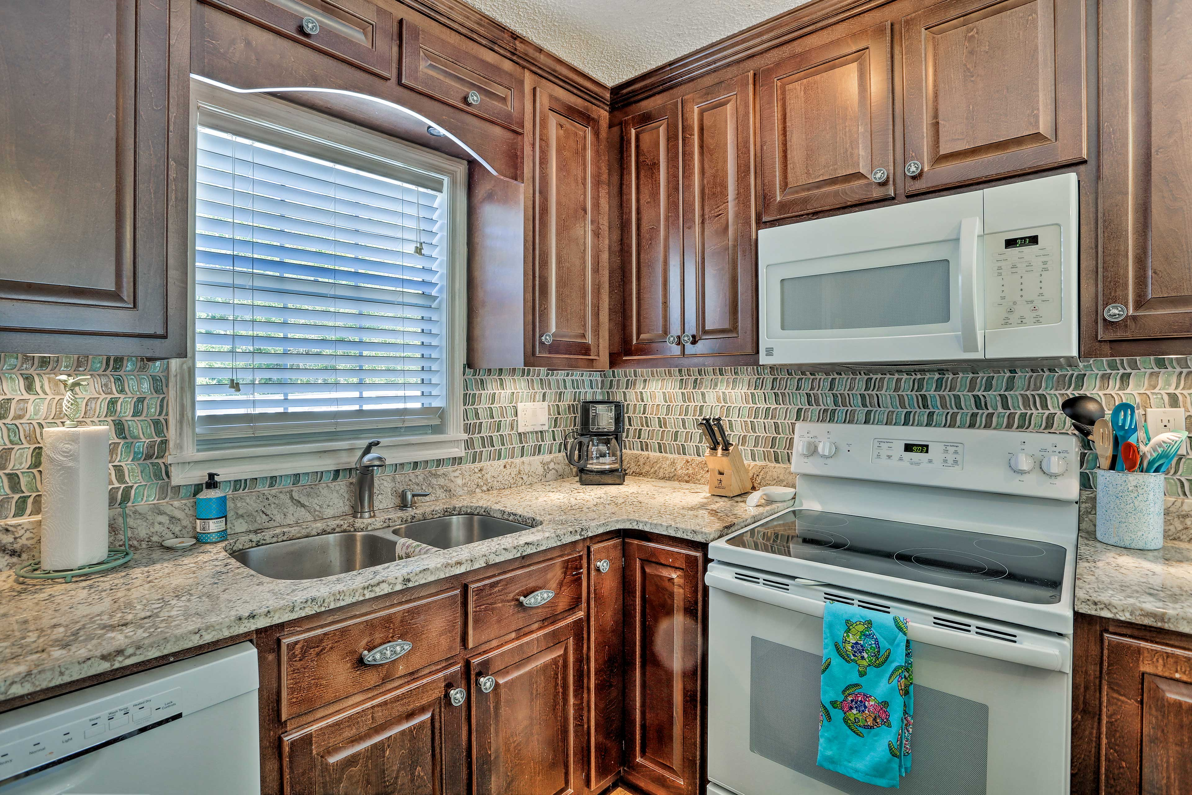 The colorful tile backsplash adds a touch of the ocean to the kitchen!
