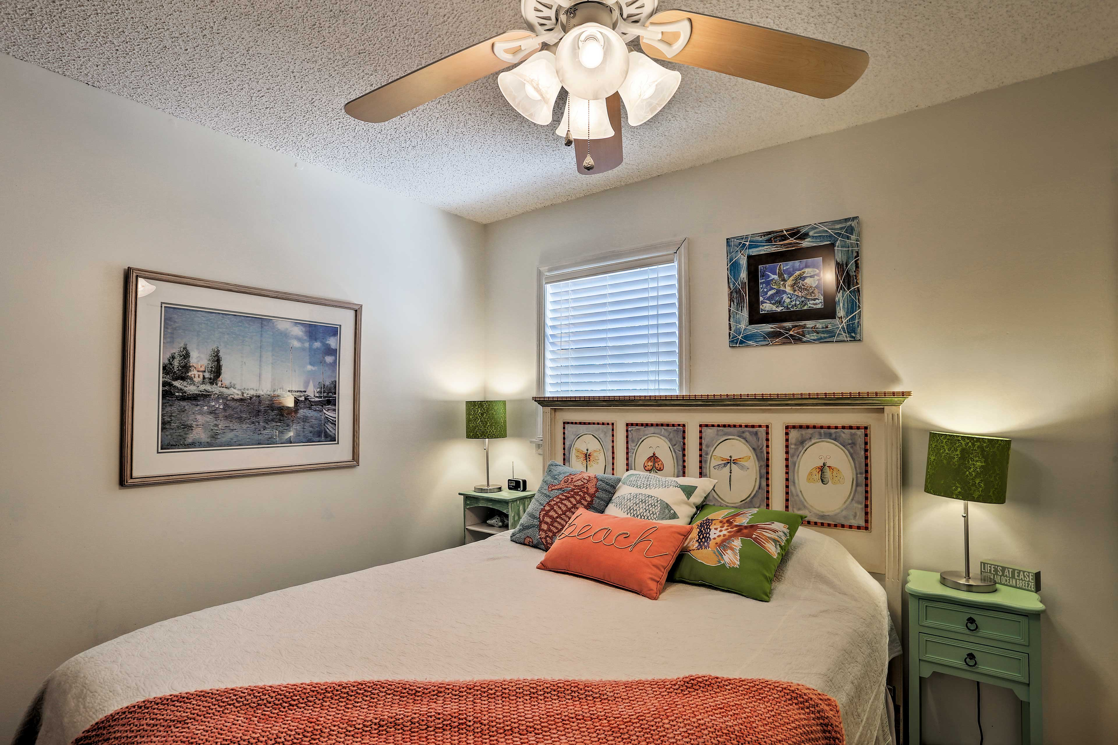 The beachy bedroom boasts a queen bed.