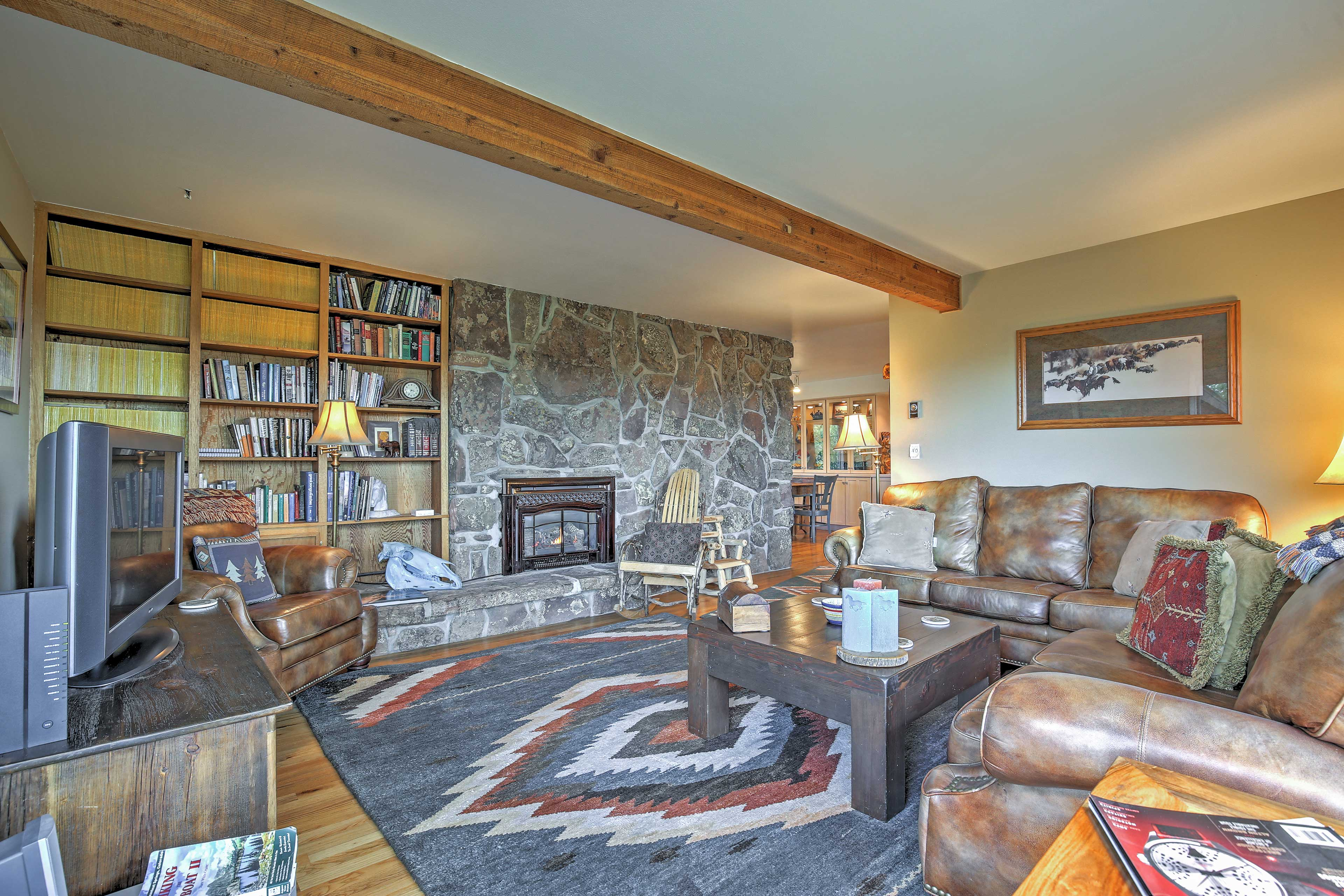 The living room features a flat-screen TV and fireplace.