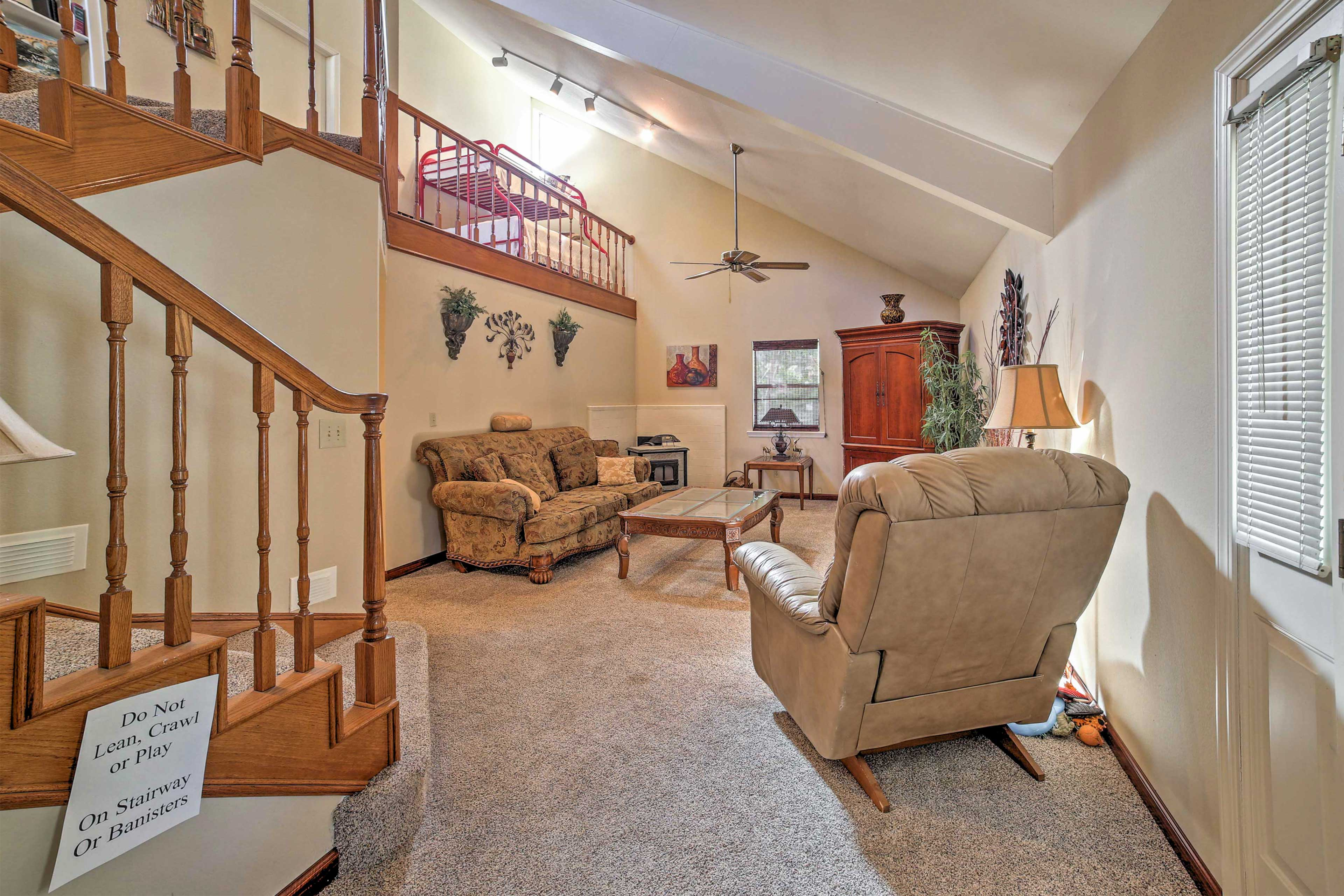 The open staircase & upstairs banister create a spacious ambiance.