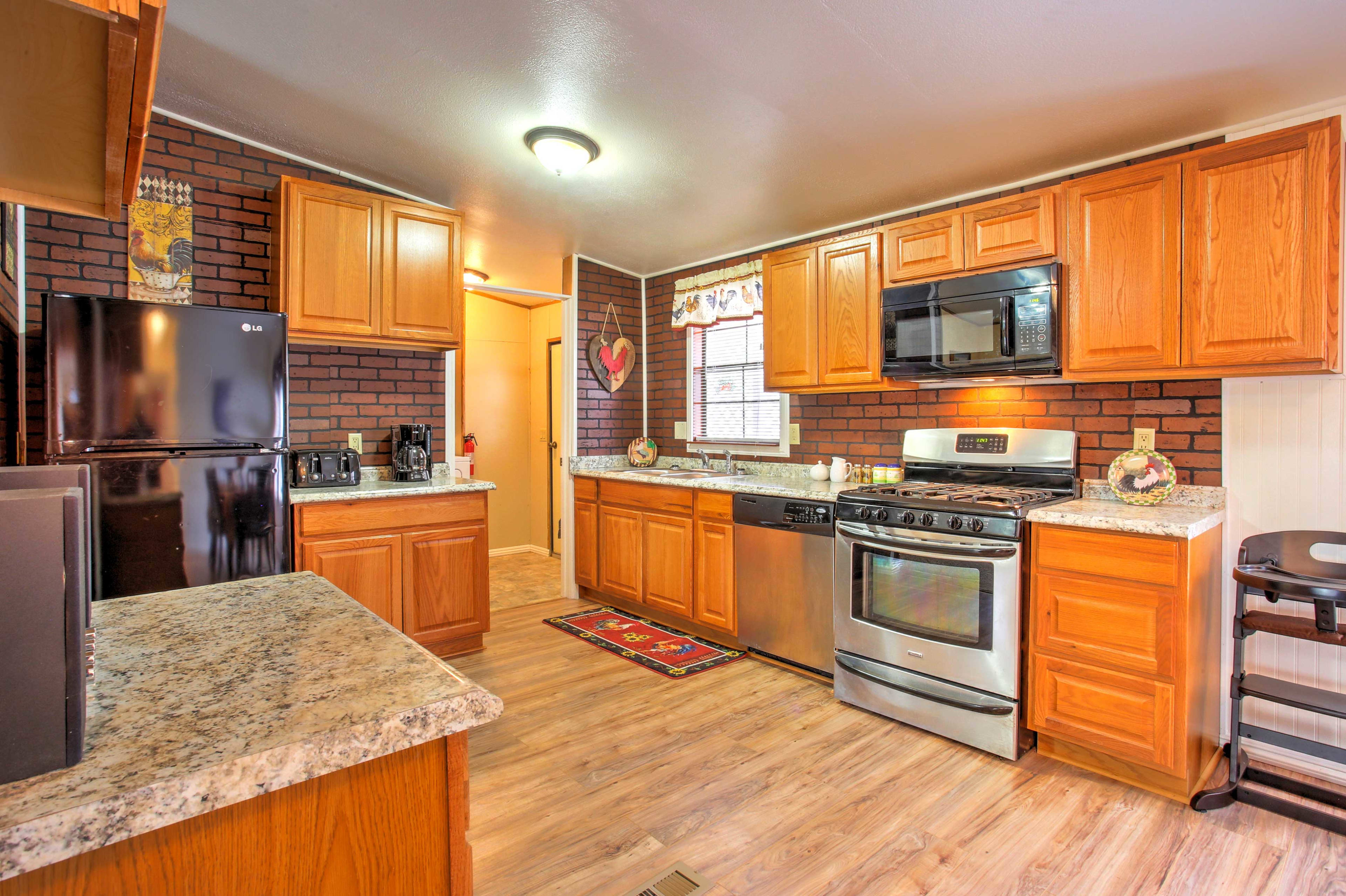 The fully equipped kitchen which features wood cabinets and beautiful countertops has everything you need to make delicious home cooked meals.