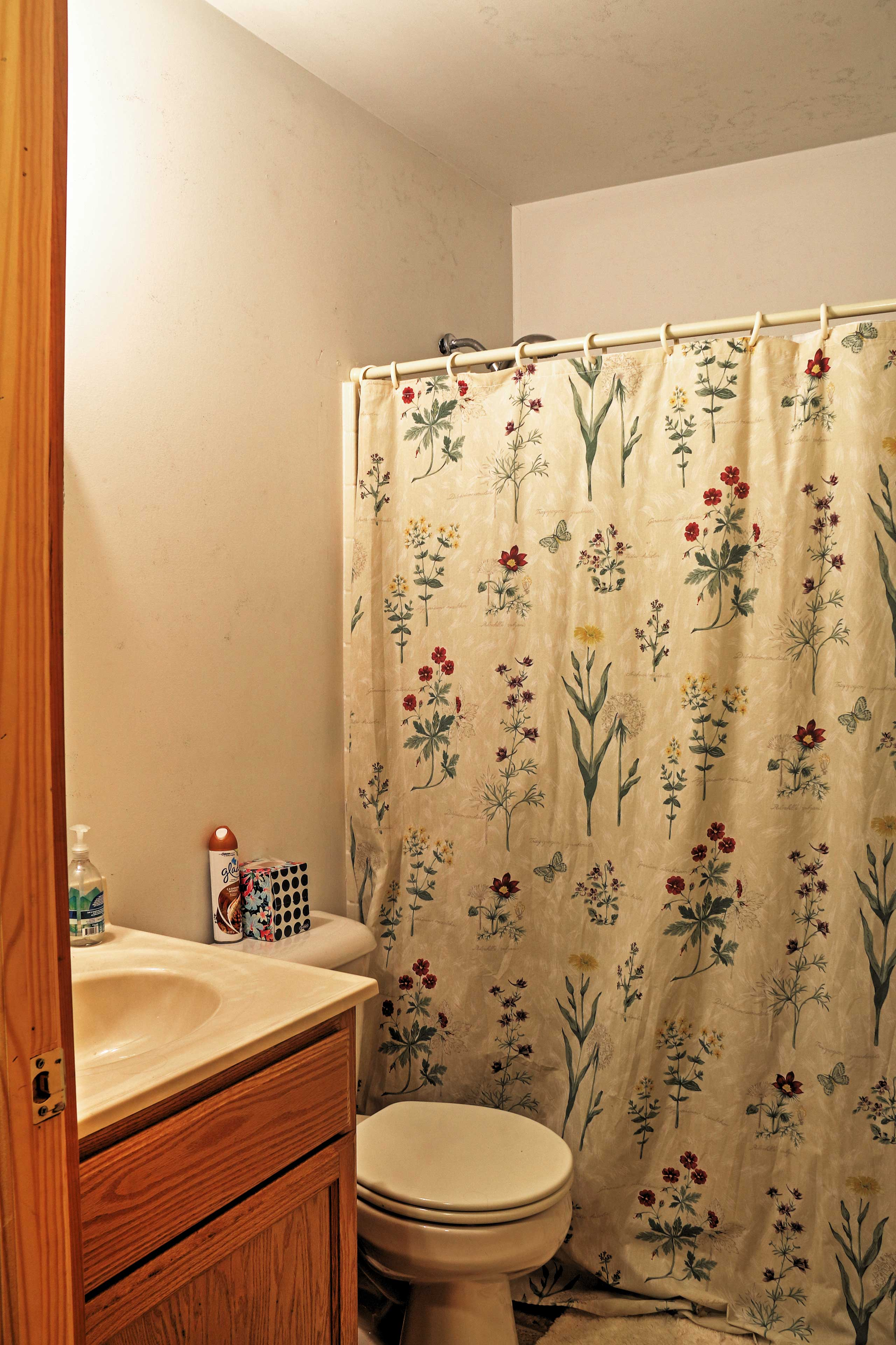 Feel fresh as a flower after rinsing off in this clean shower, decorated with a floral curtain.