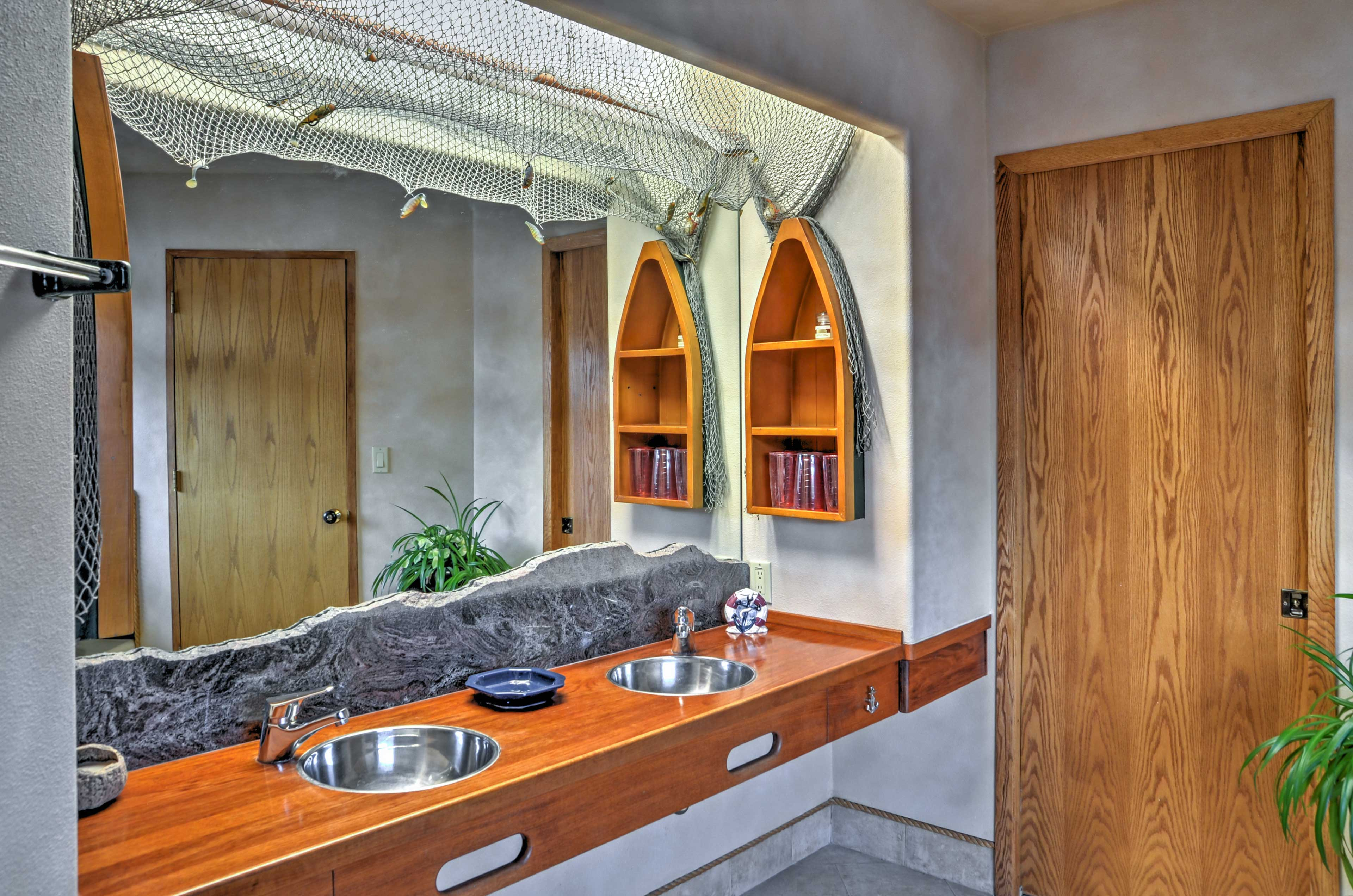 Get read for the day in this lake-themed bathroom with double vanities.