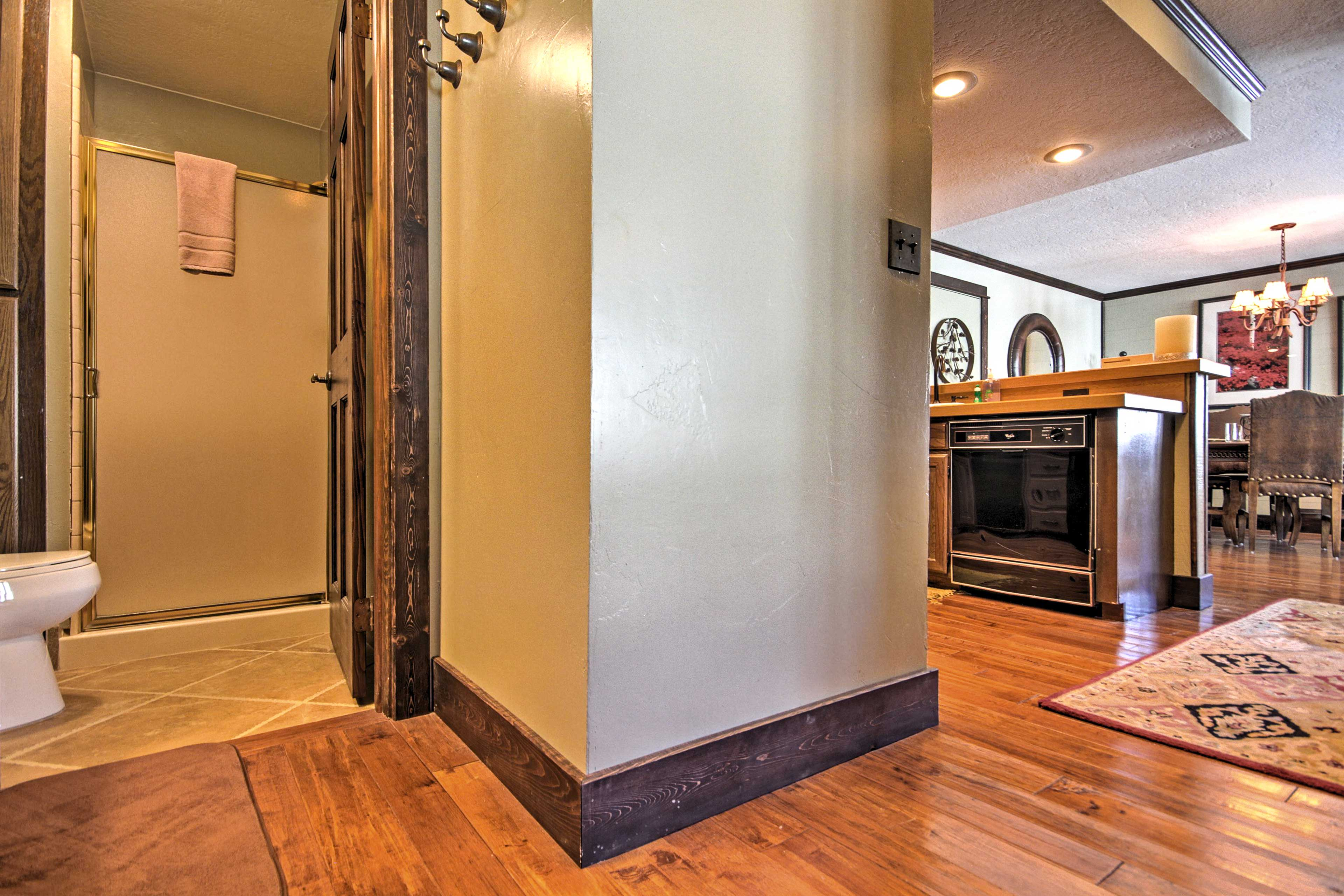 Wood planked floors run throughout the kitchen, dining area, and living area.