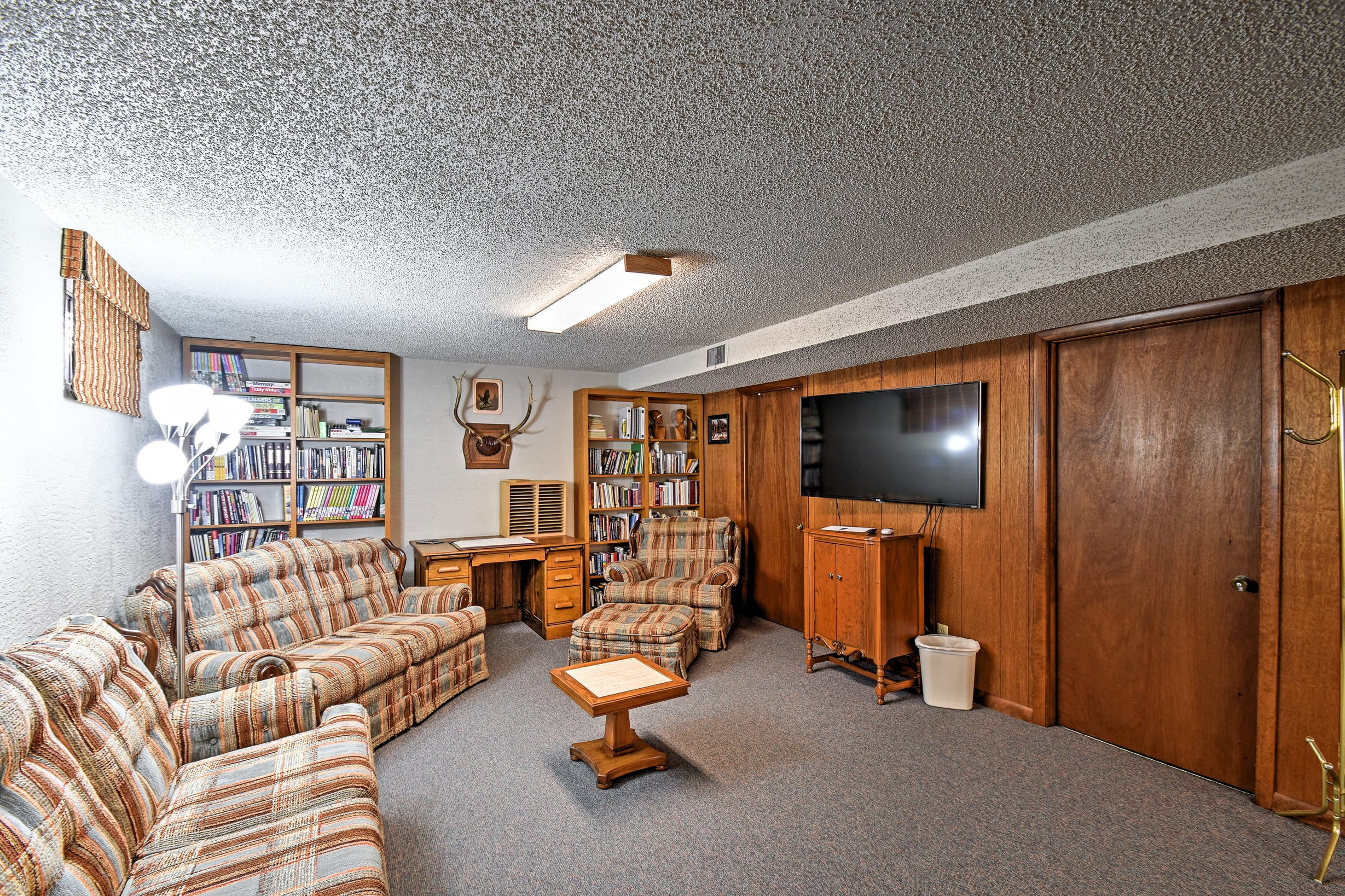 The downstairs recreation room has a TV, couch, books and a ping pong table.