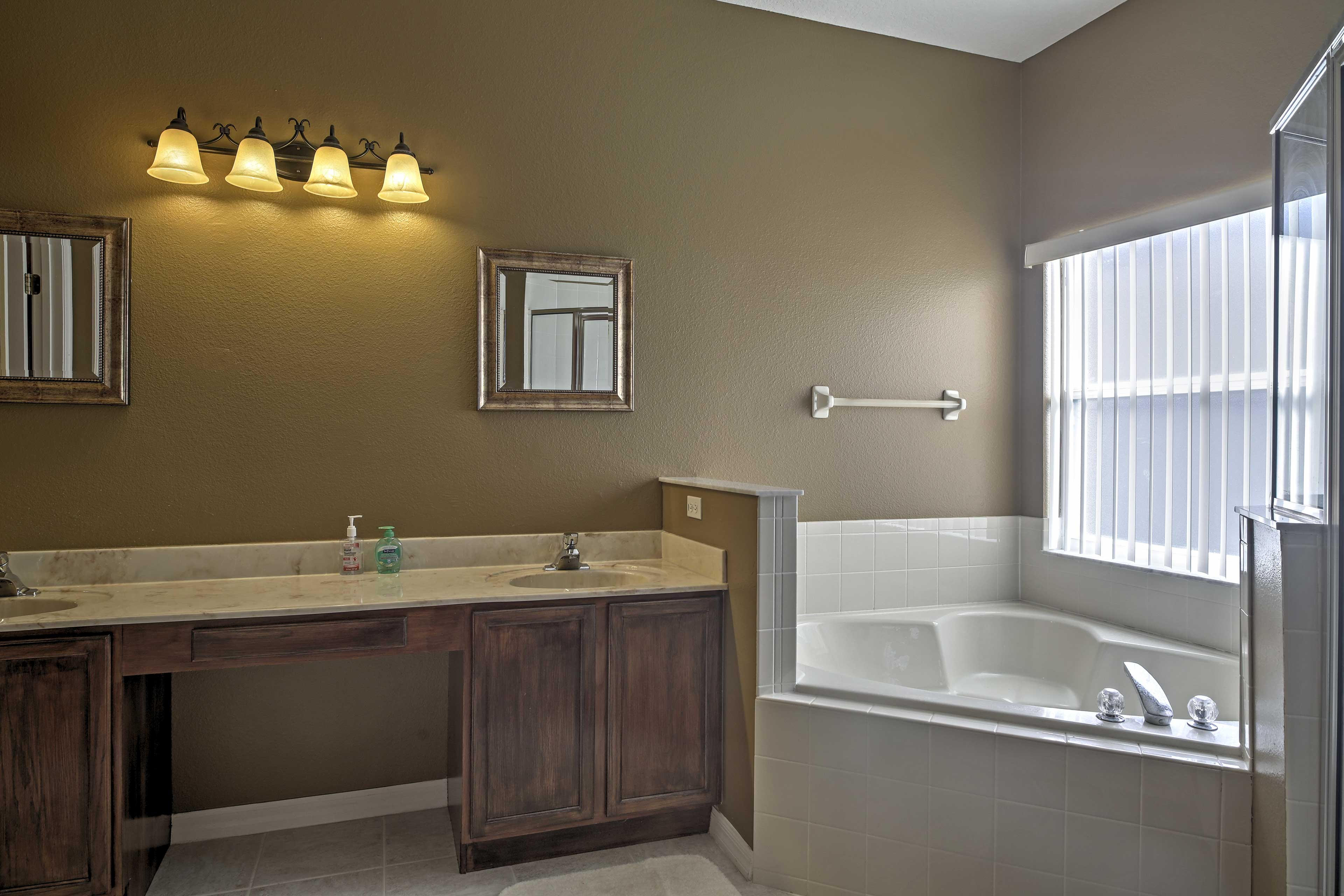 Freshen up in the bath tub or shower in this pristine master bathroom.