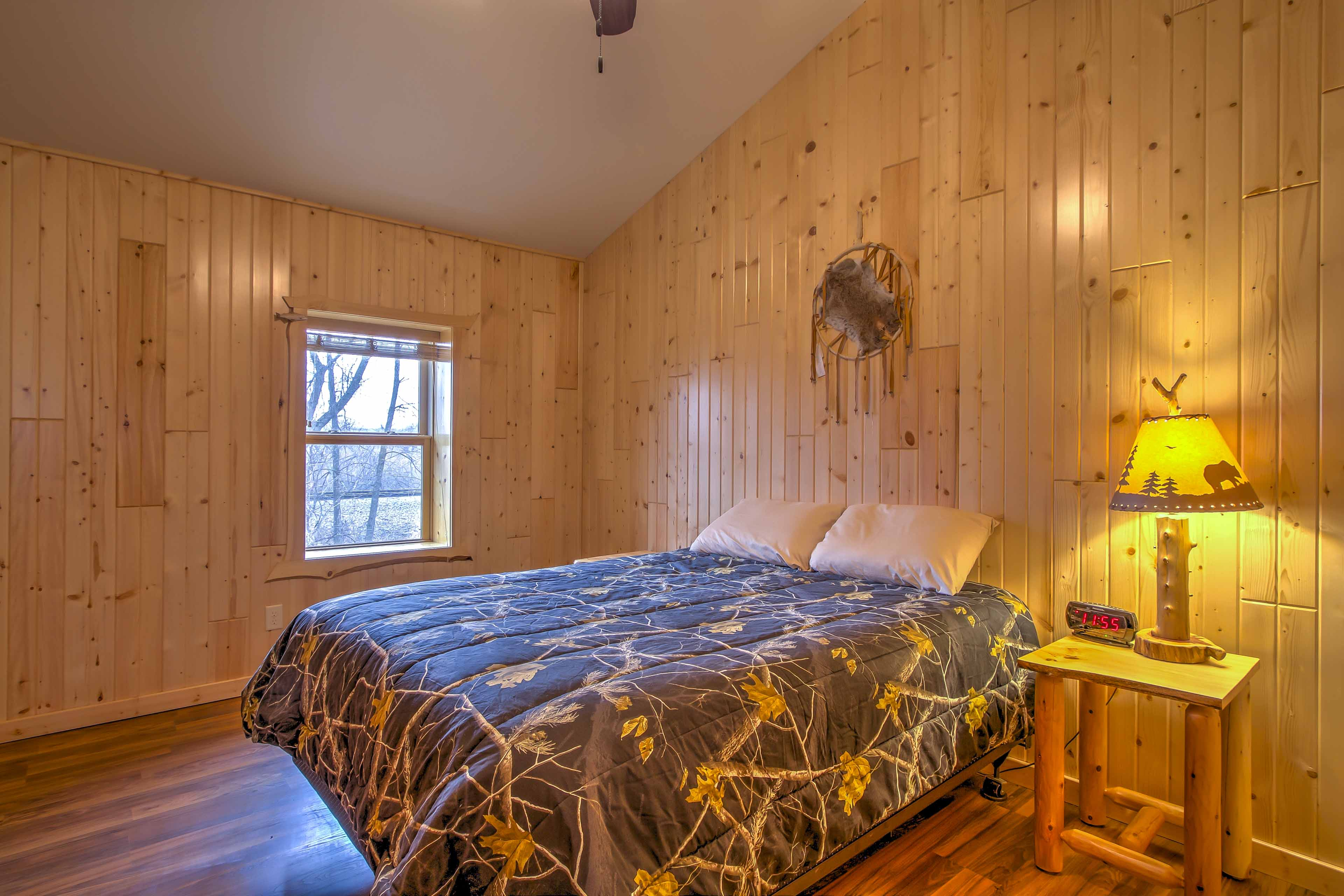 This bedroom features a queen-sized bed and simple mountain decor.