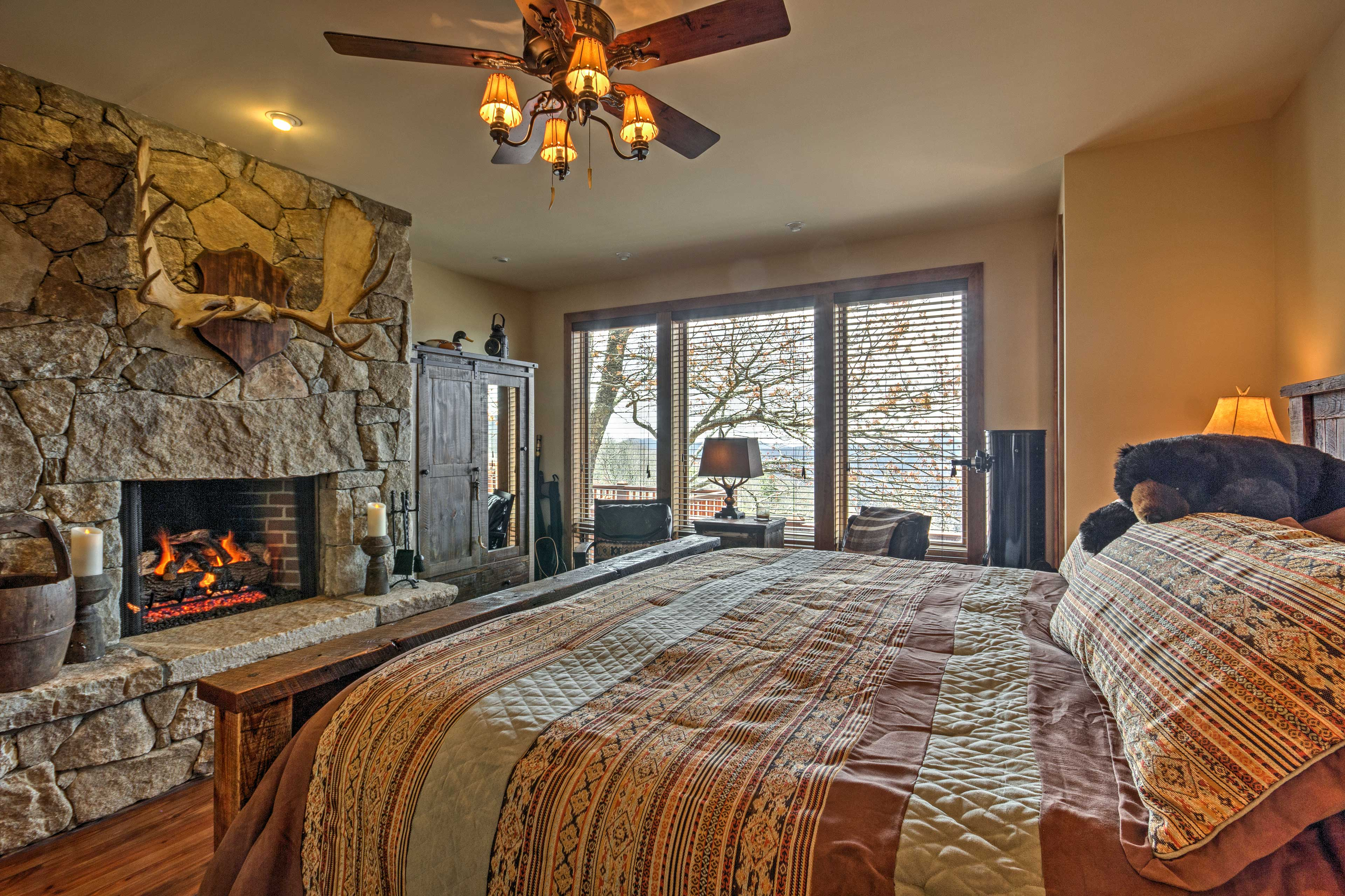 The master bedroom is complete with a king-sized bed and stone fireplace.