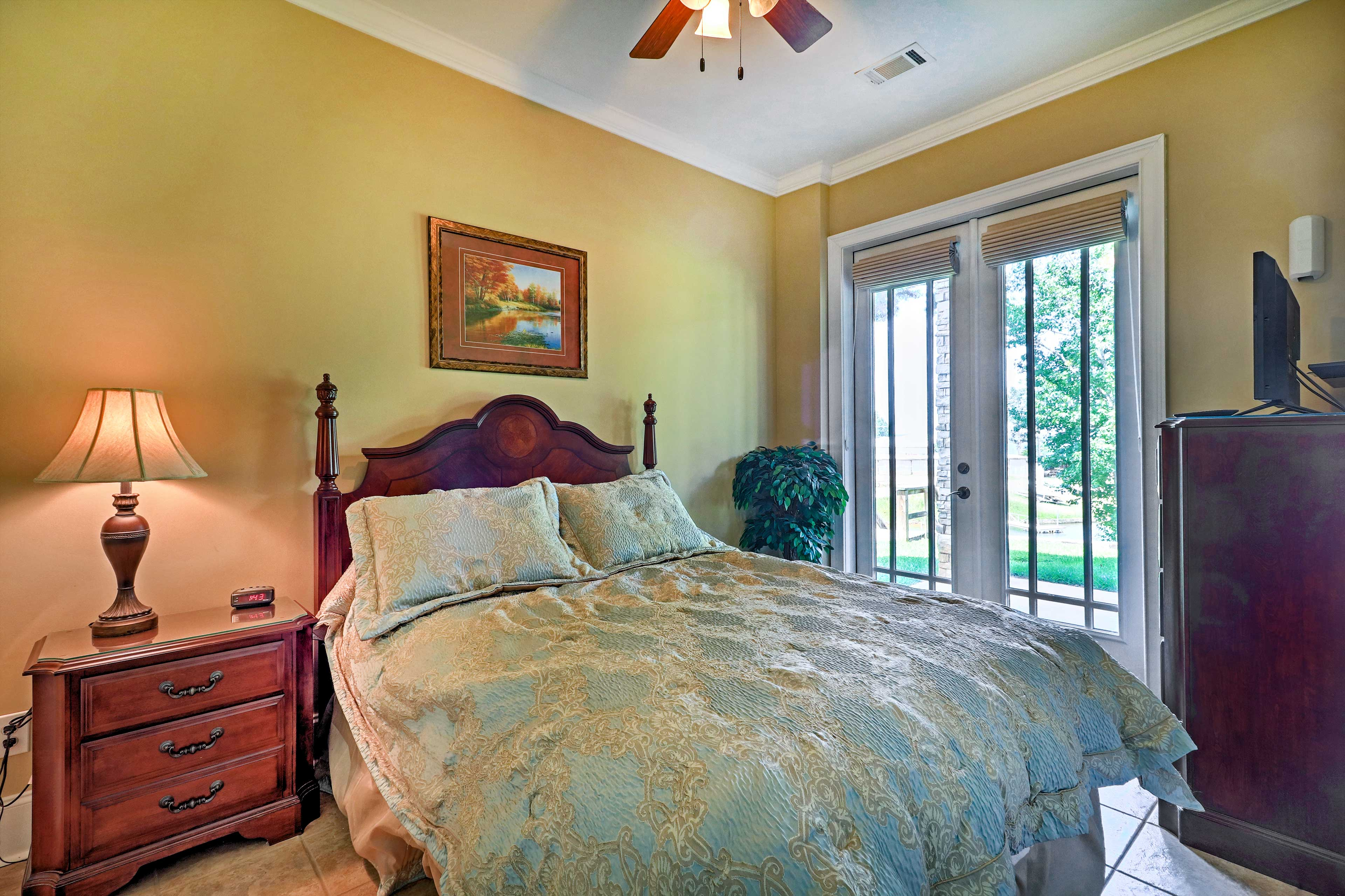 This bedroom features a queen bed and double french doors leading to the backyard.