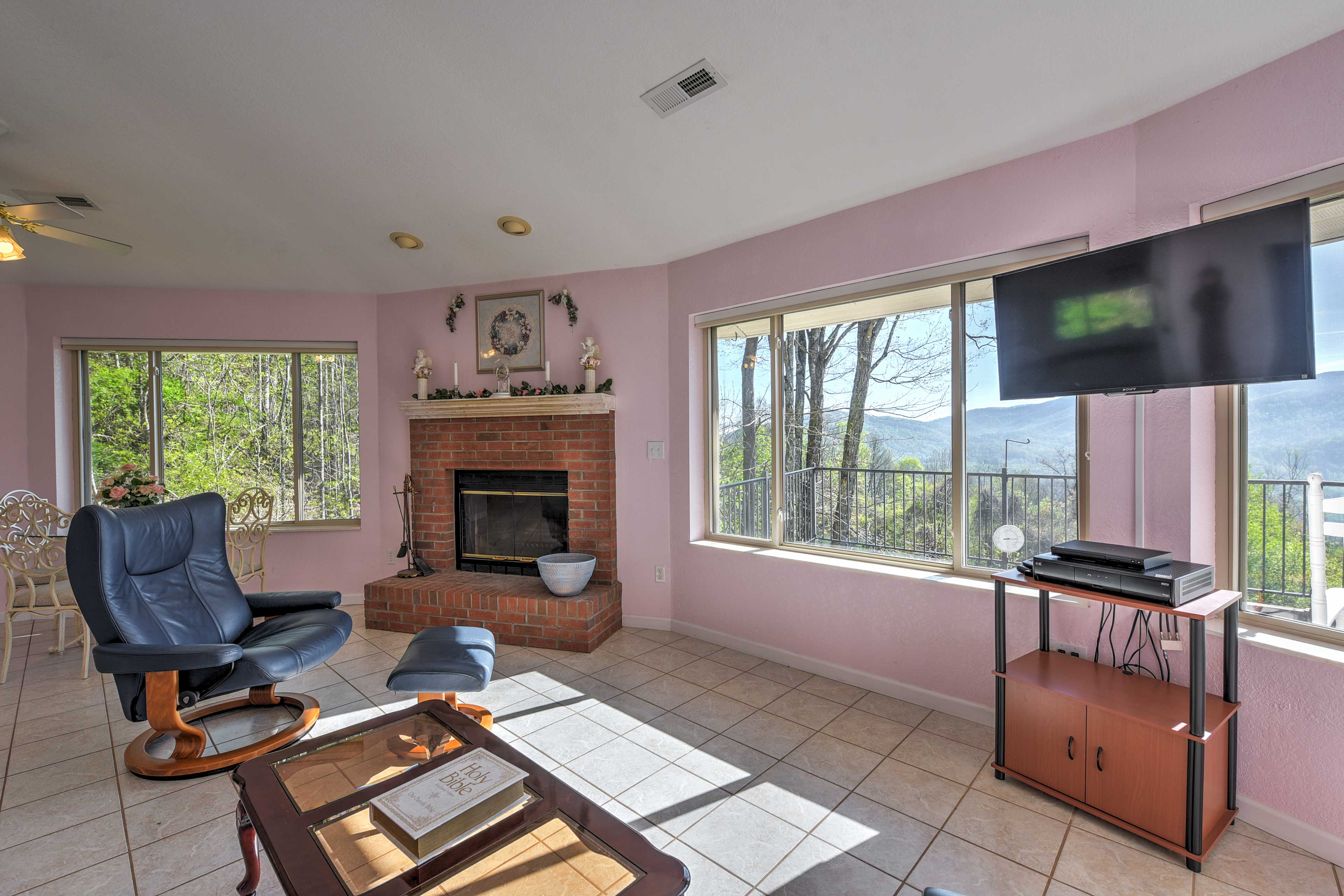 The room features plenty of seating and a red brick wood-burning fireplace.