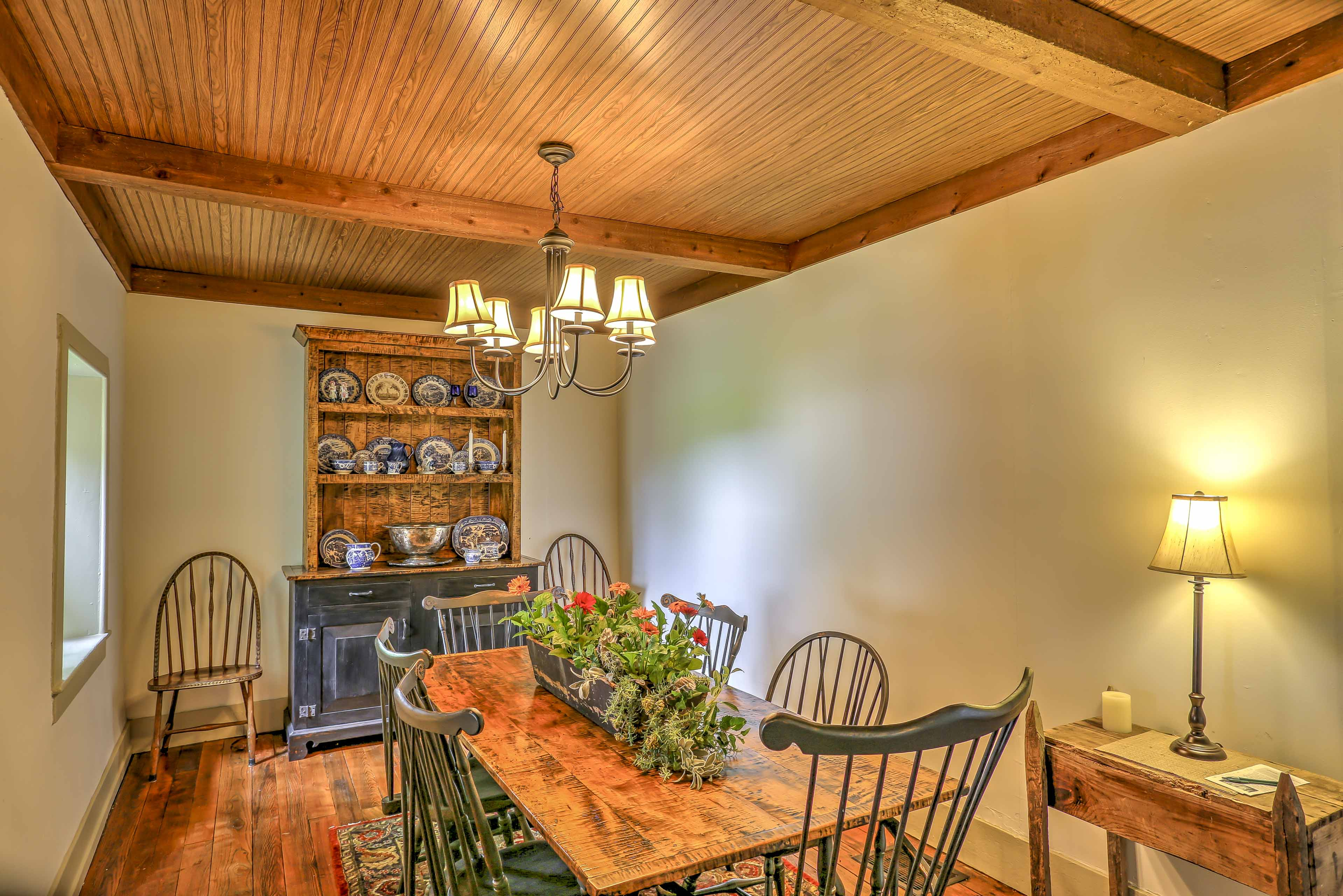 The formal dining room boasts an elegant finished-wood table with seating for 8 and a rustic china cabinet.