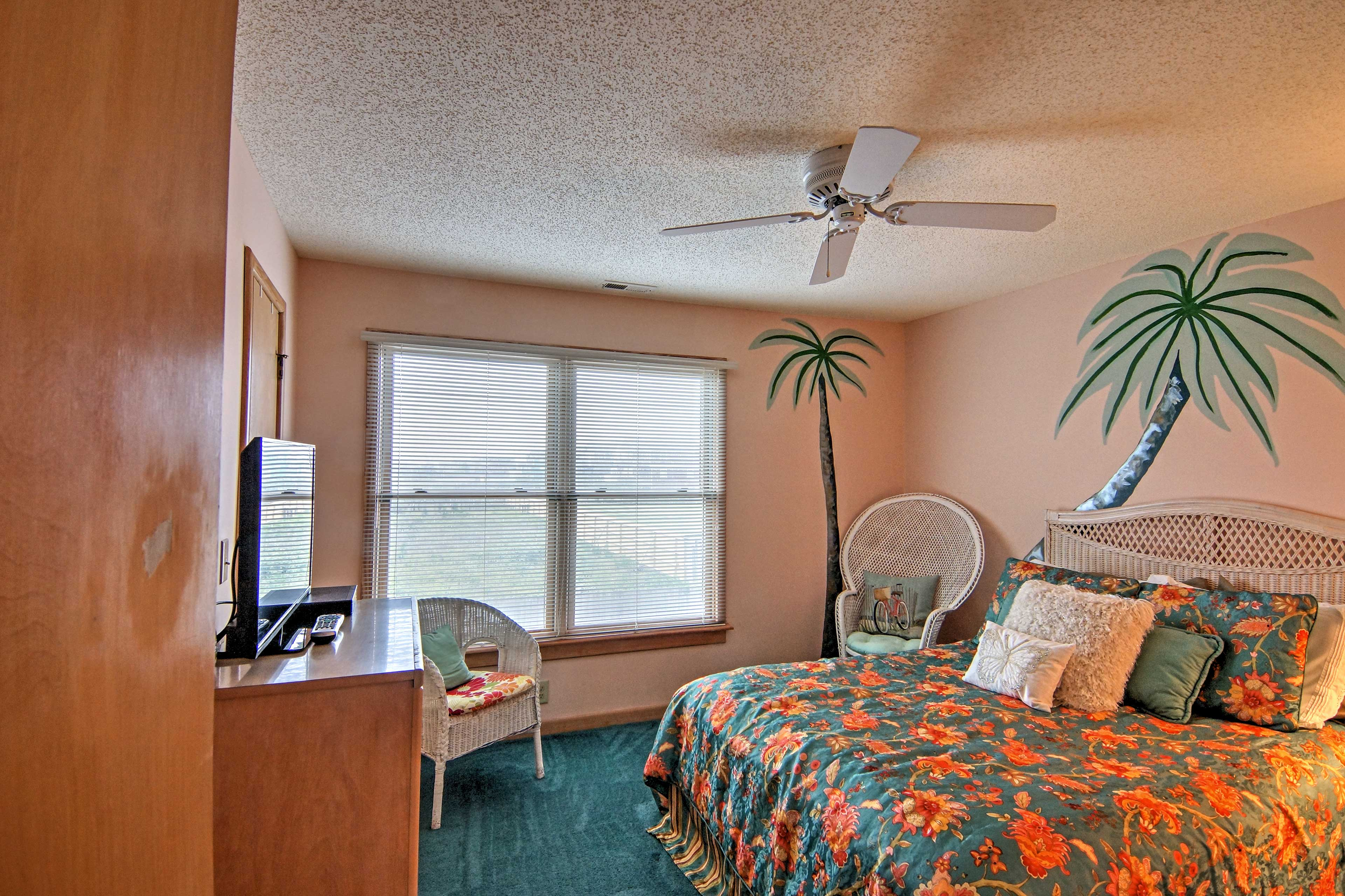 The 'Palm Room' features a comfortable queen-sized bed and flat-screen TV.