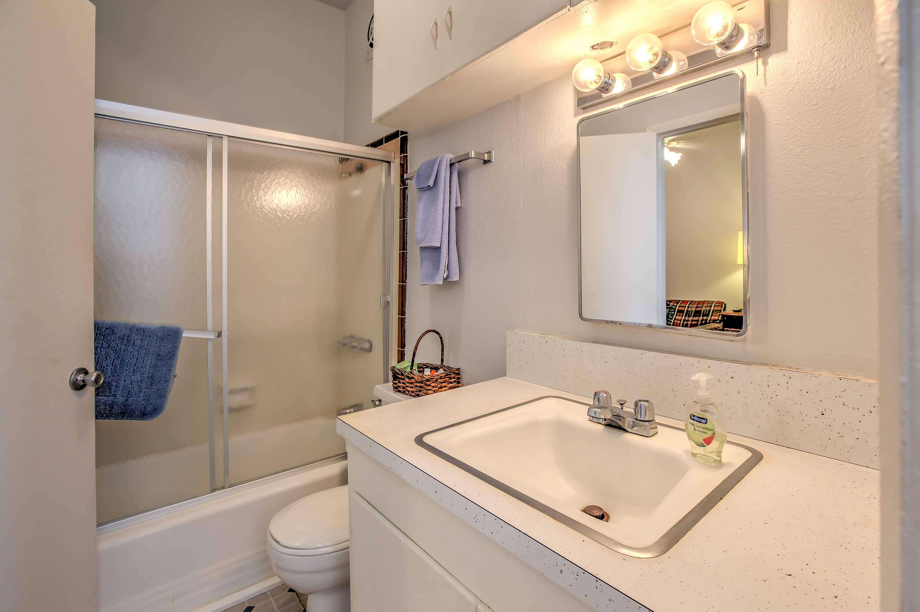The first bathroom offers a pristine vanity and shower/tub combo.