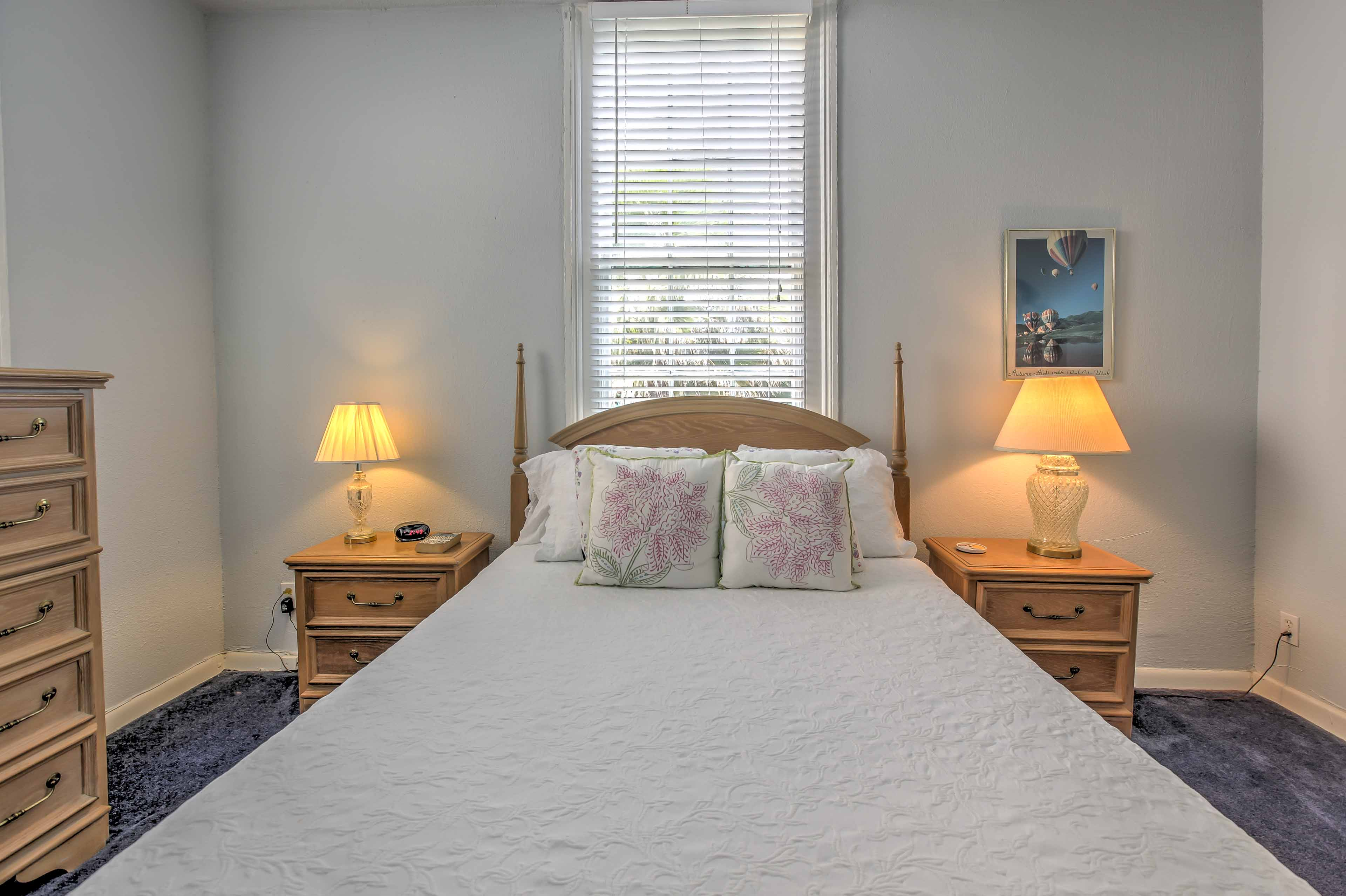The well-furnished master bedroom features a comfortable queen-sized bed.