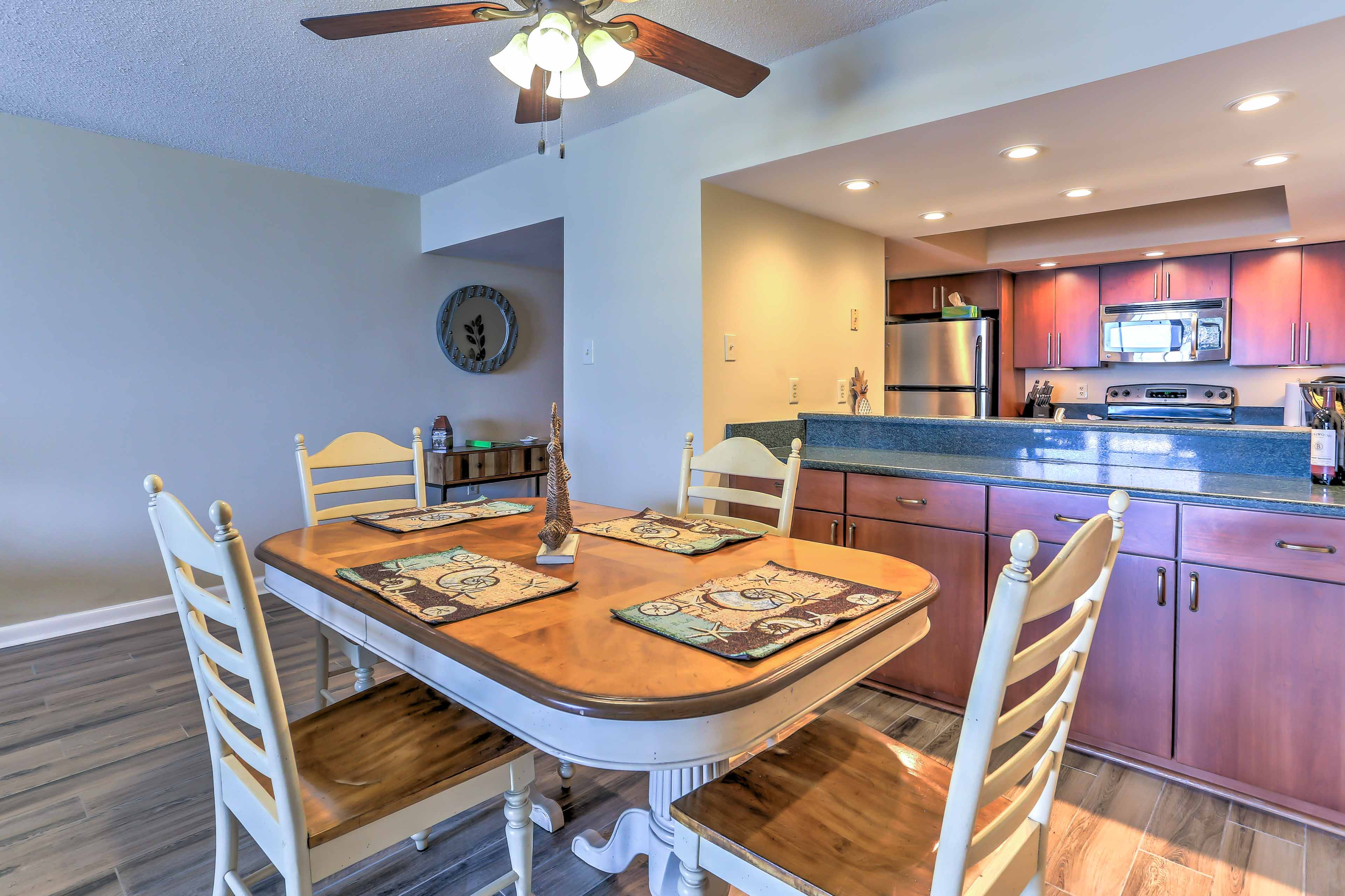 Gather around the dining table set for 4 to enjoy your meals with the group.