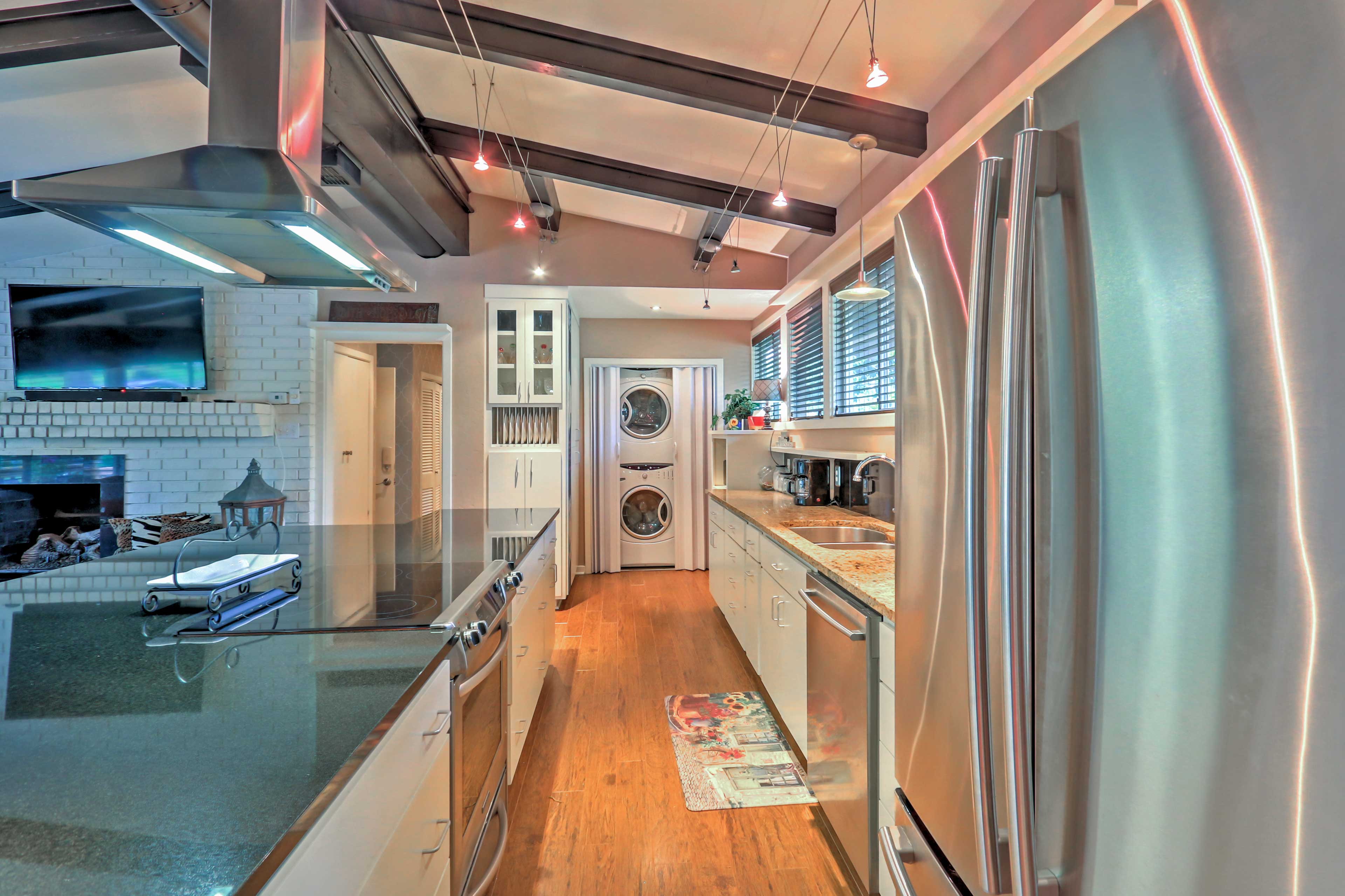 The fully equipped kitchen opens to the laundry closet.