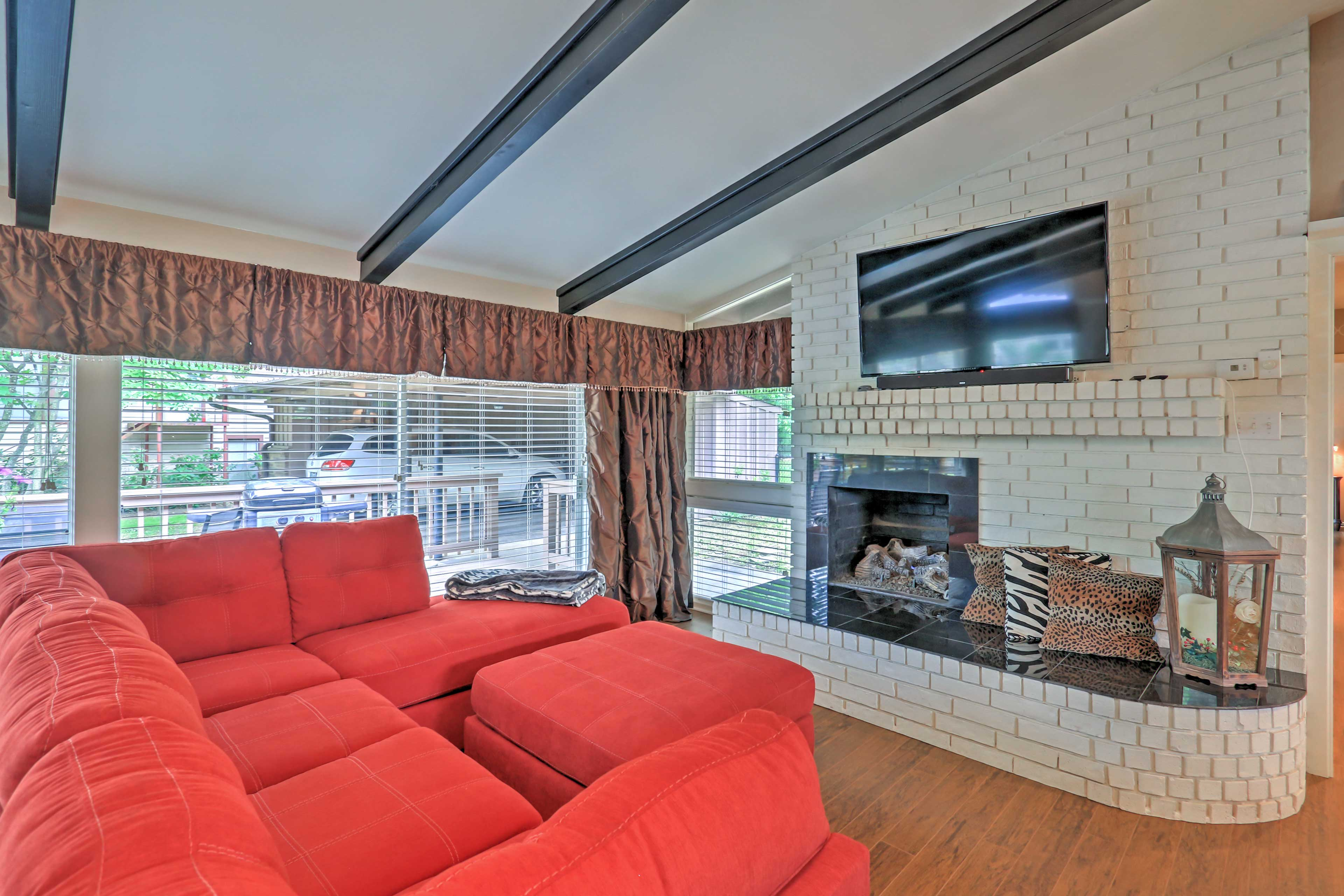 The open living room includes a large sectional couch and a gas log fireplace.