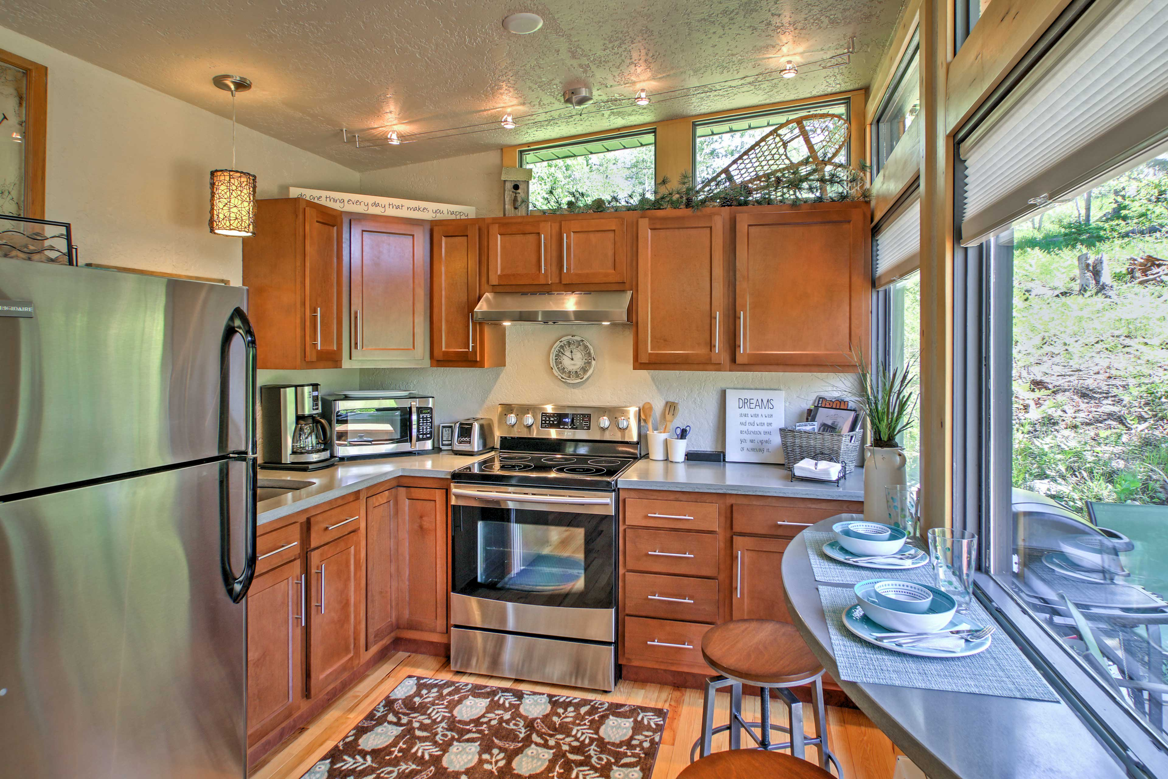 The full kitchen boasts pristine counter and modern stainless steel appliances.