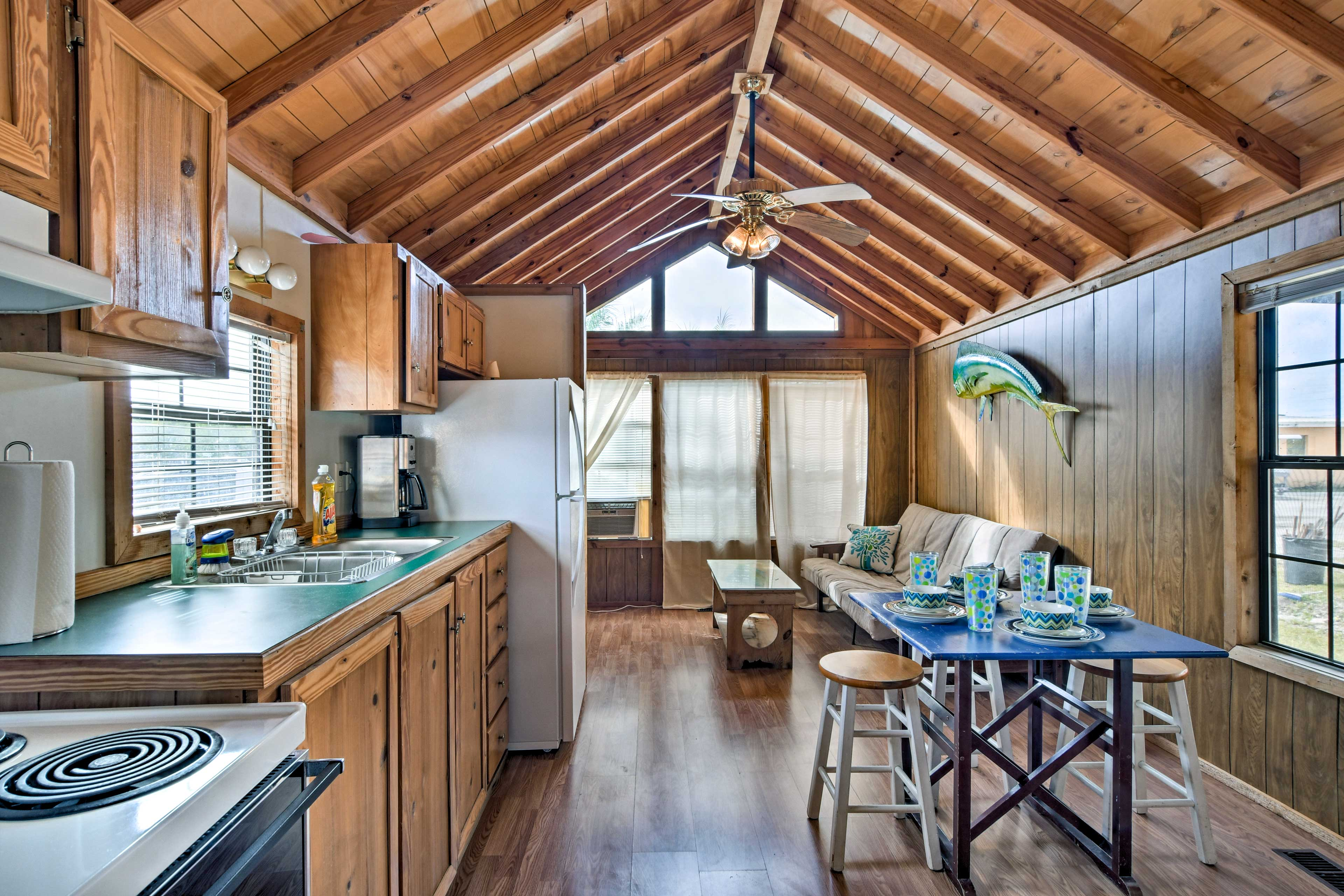 Vaulted ceilings and a wall lined with windows give this quaint cabin an open and spacious feel.
