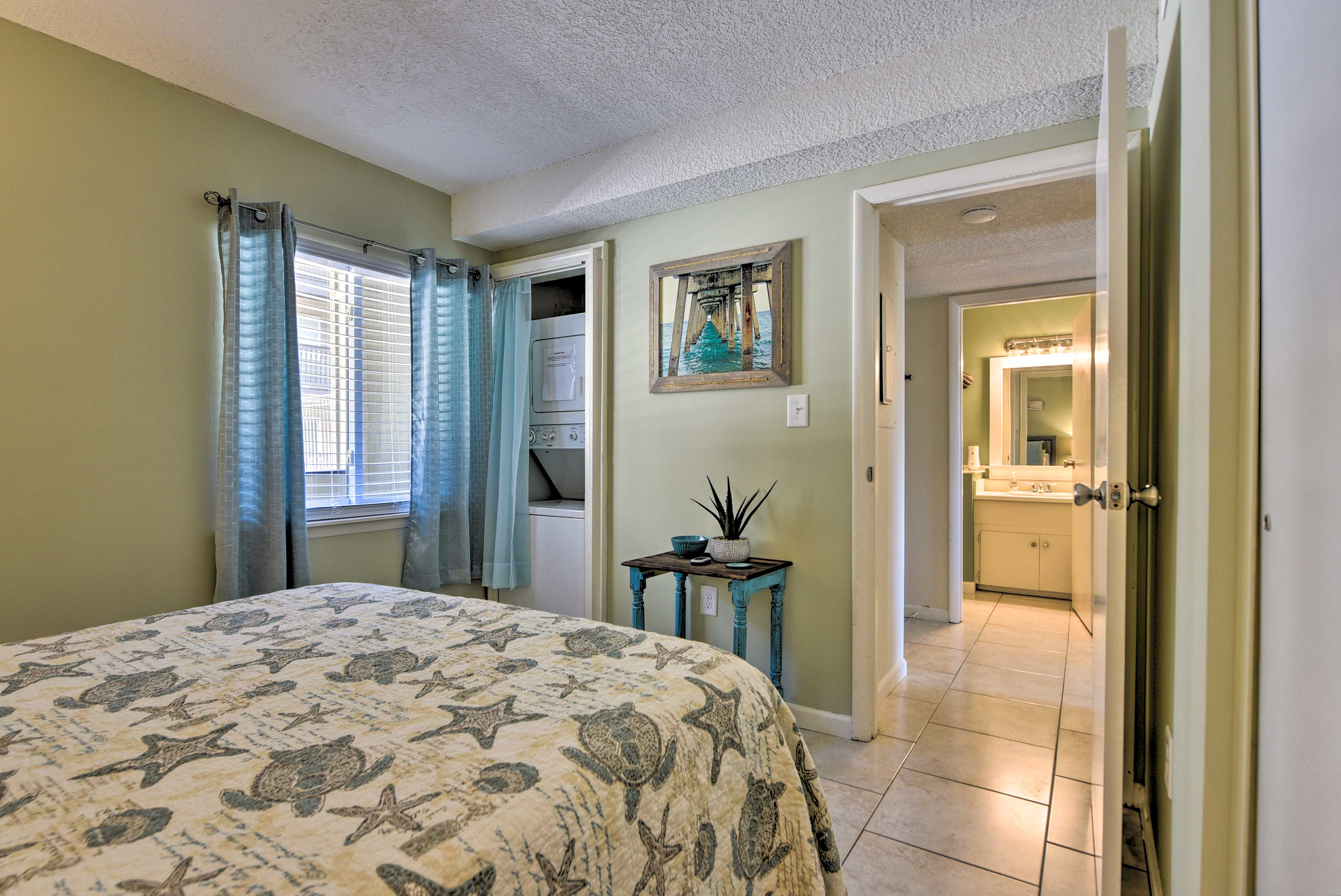 This bedroom also includes a stacked washer/dryer.
