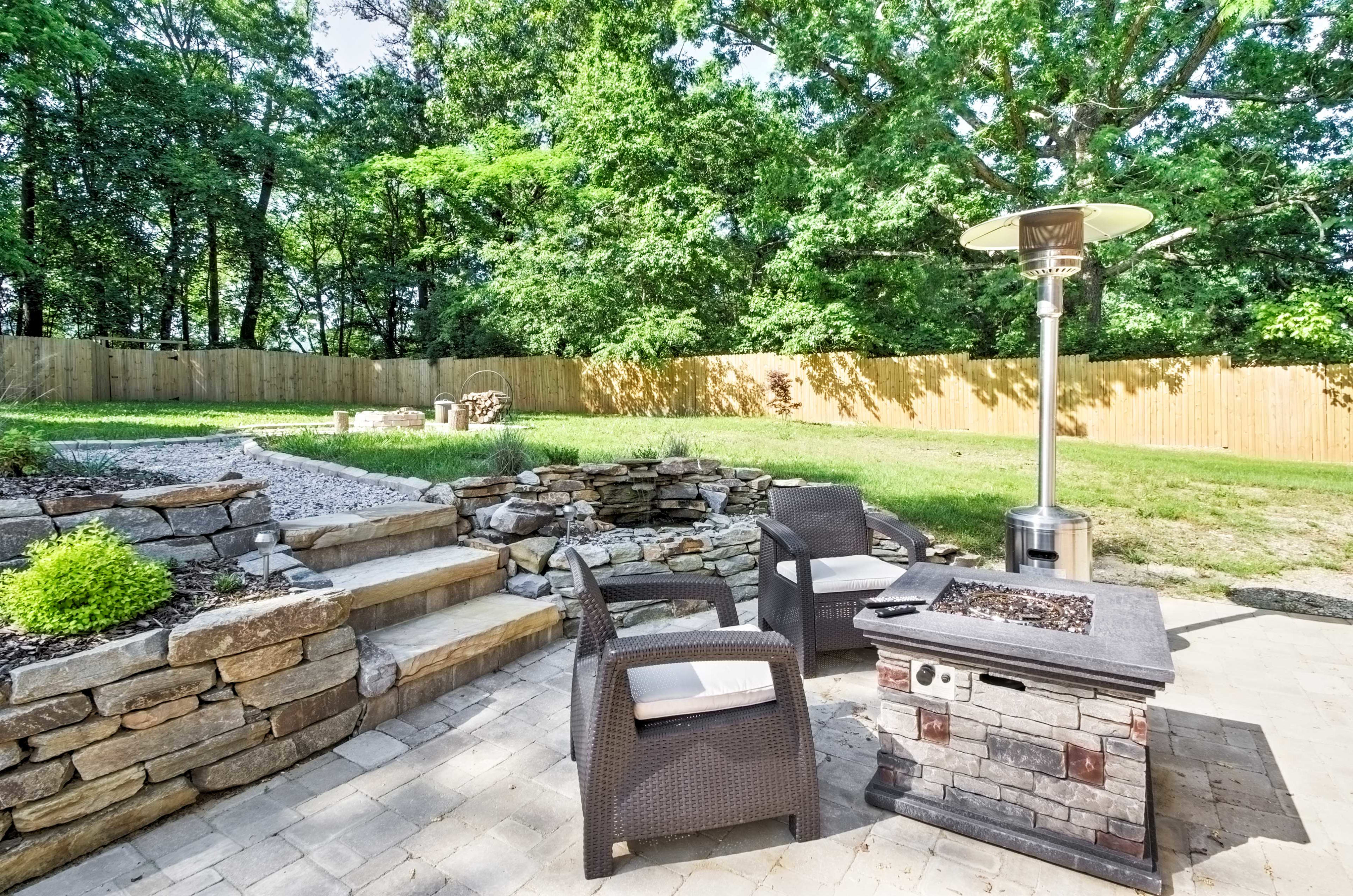 The spacious and manicured yard offers a great seating area, outdoor fire pit and sauna.