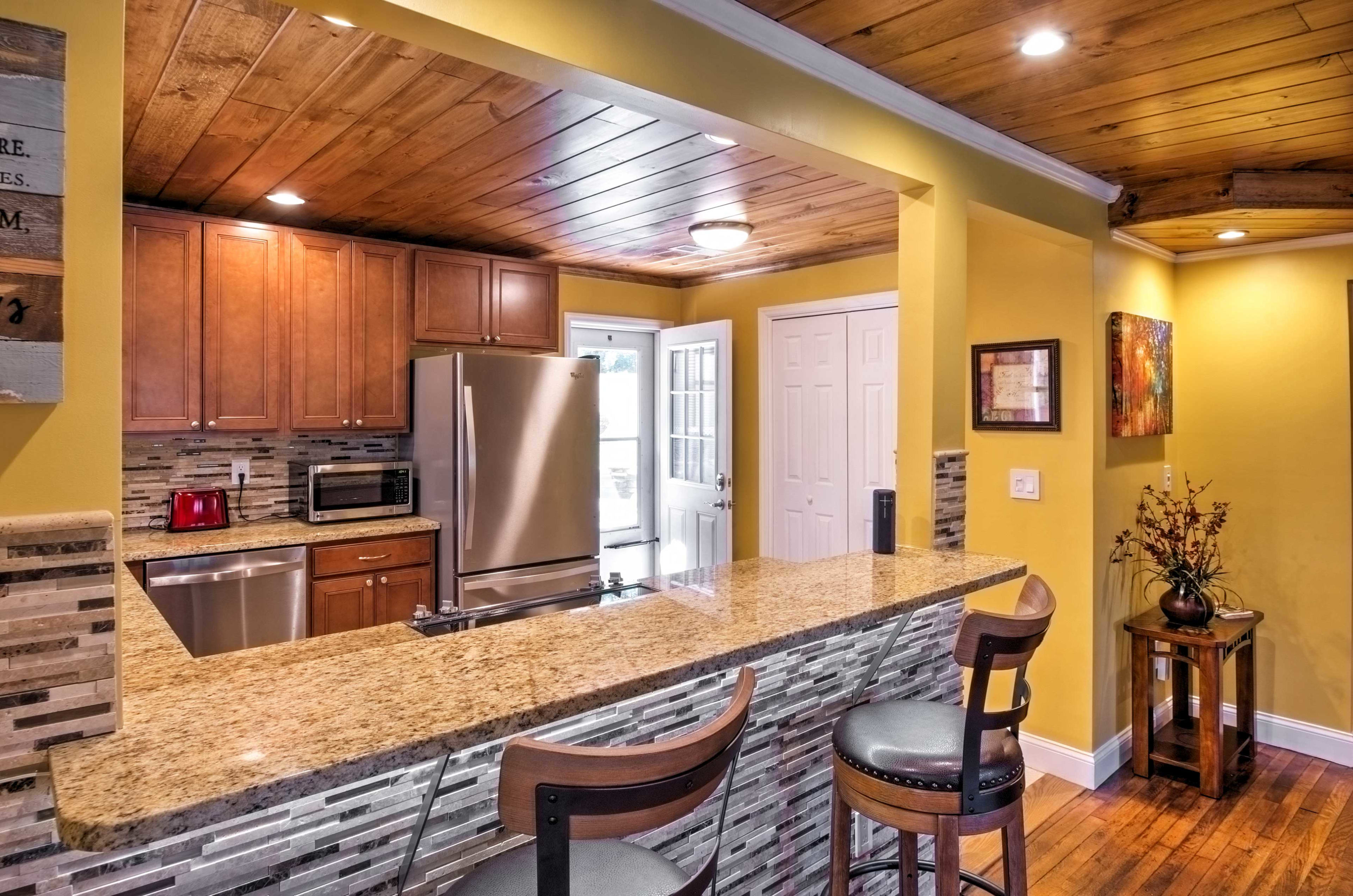 The updated kitchen features stainless steel appliances, beautiful wood cabinets and breakfast bar.