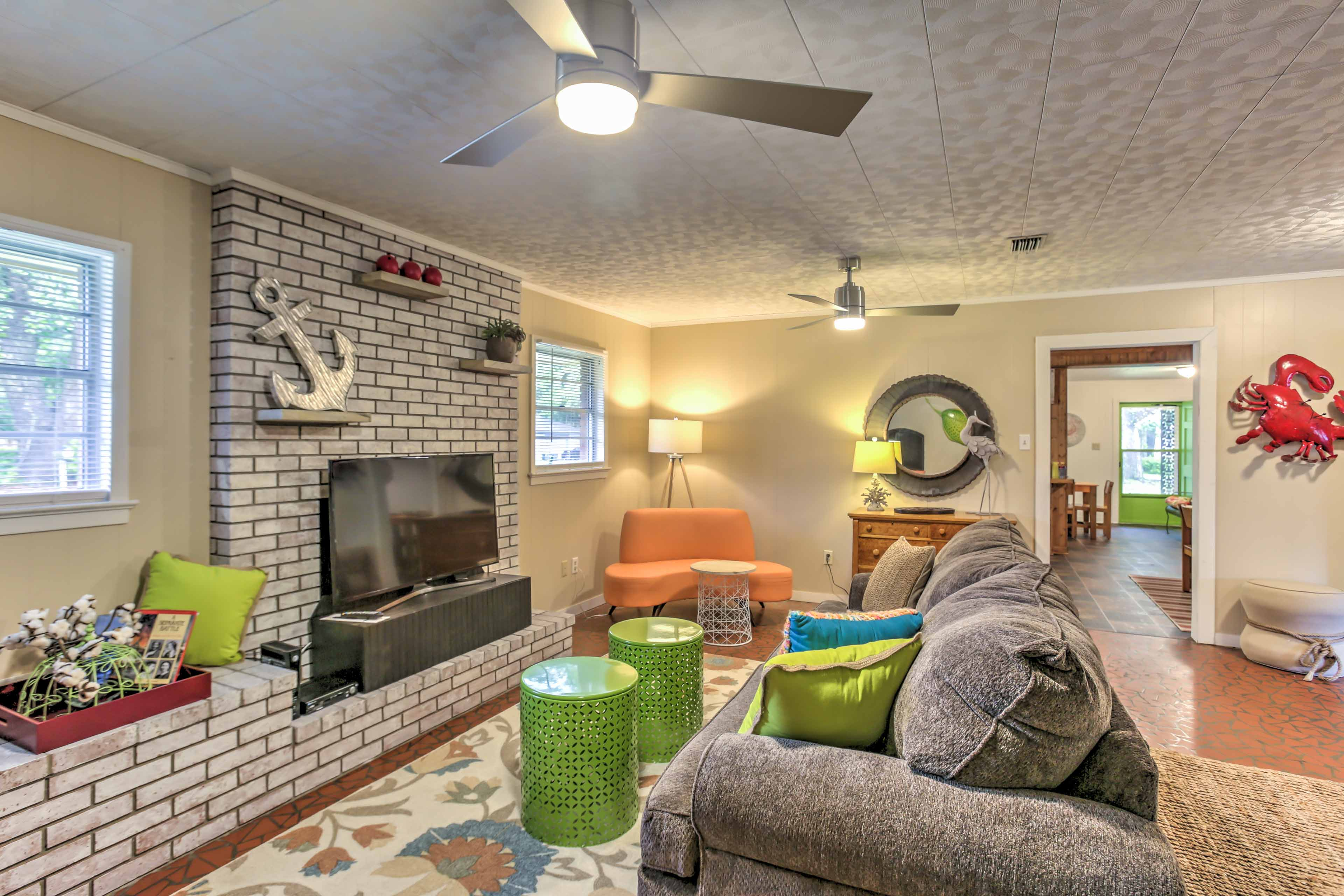 Make yourself at home in this inviting living room, brightly decorated with vibrant colors and beach-themed accents.