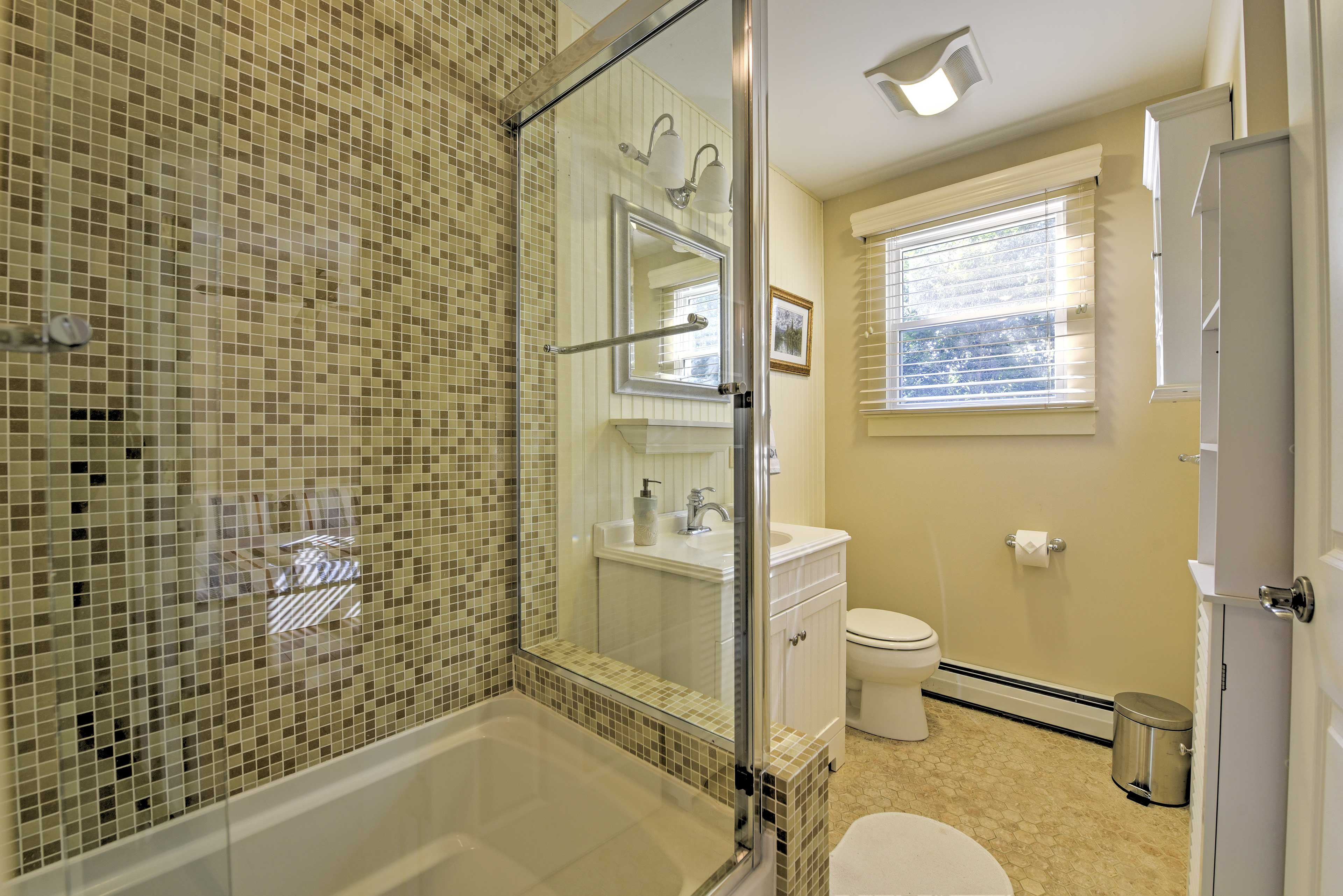 The full bathroom is equipped with a tiled tub-shower combo.