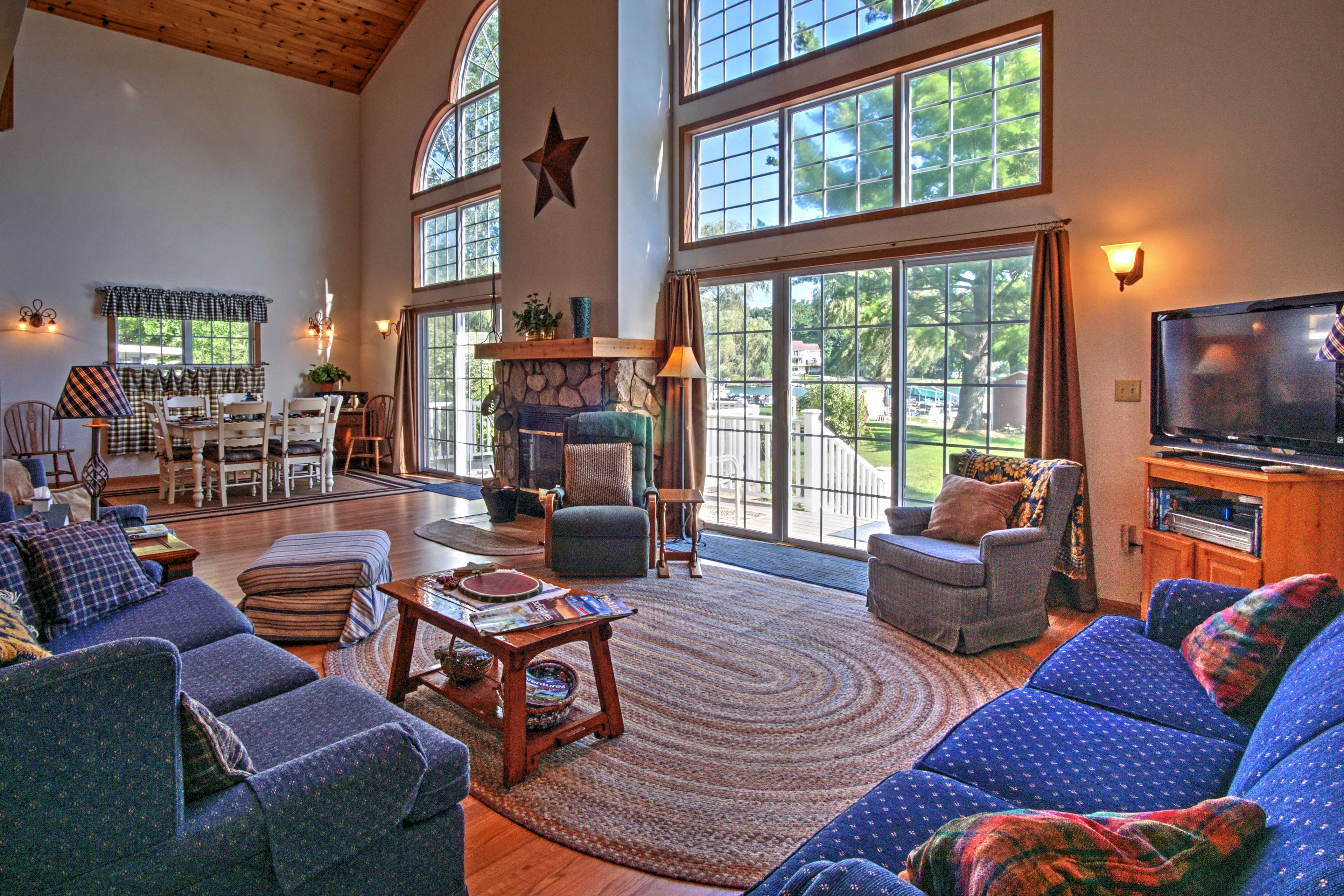 A wall of windows and wood-paneled cathedral ceilings line the great room.