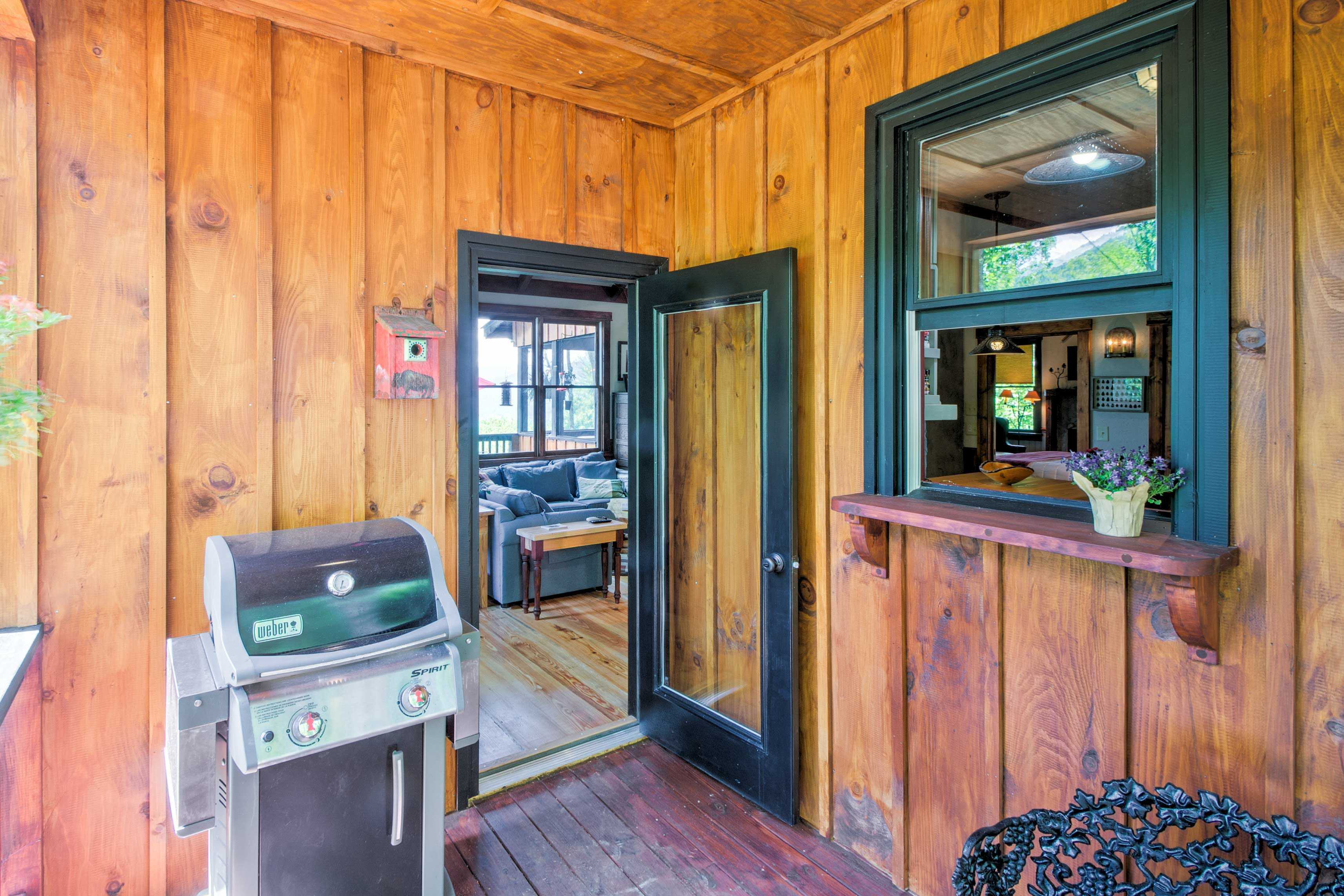 This covered cook porch off the kitchen features a pass-through window and gas grill.