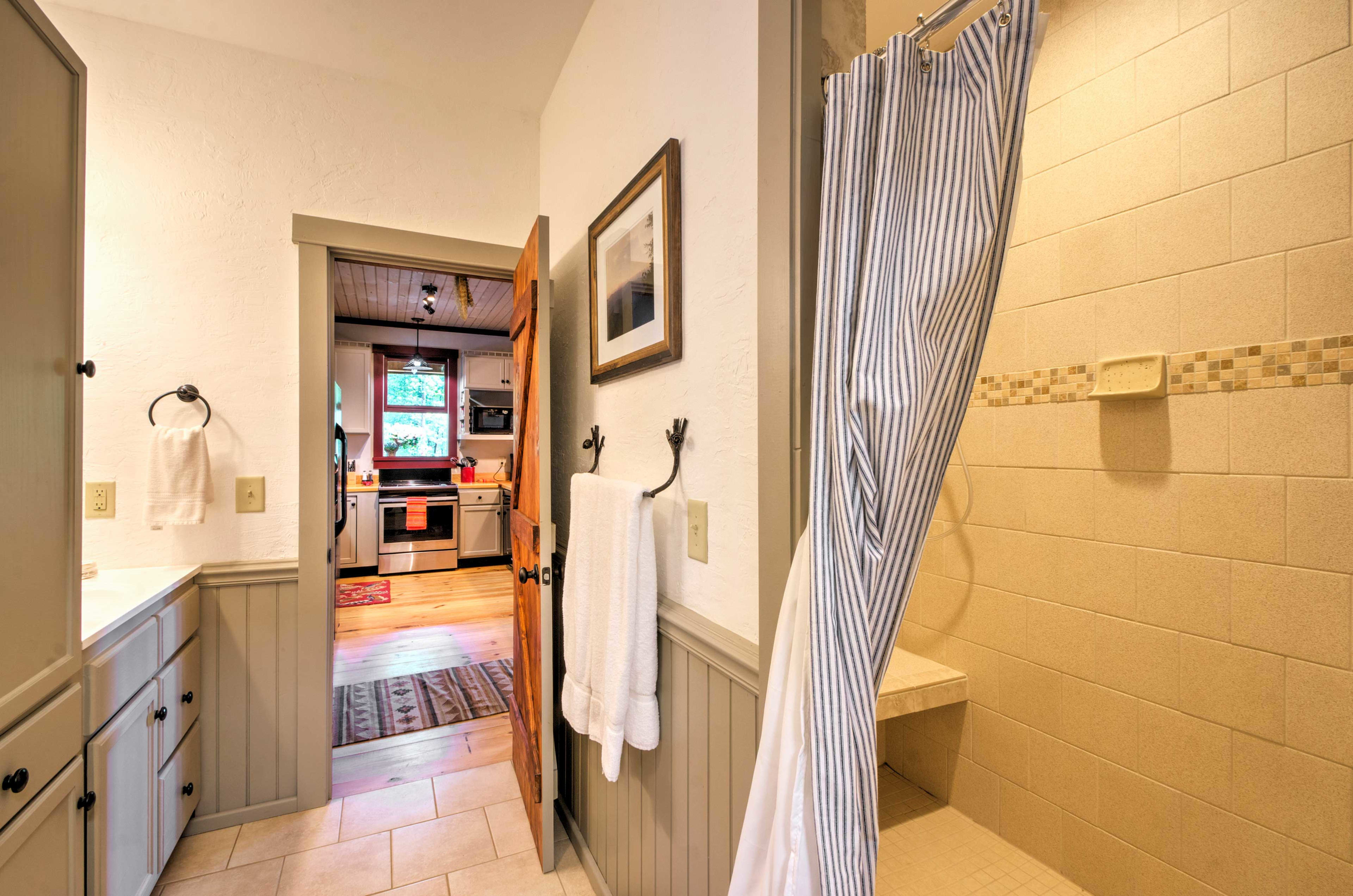 This large walk-in shower features a bench and 2 shower heads.
