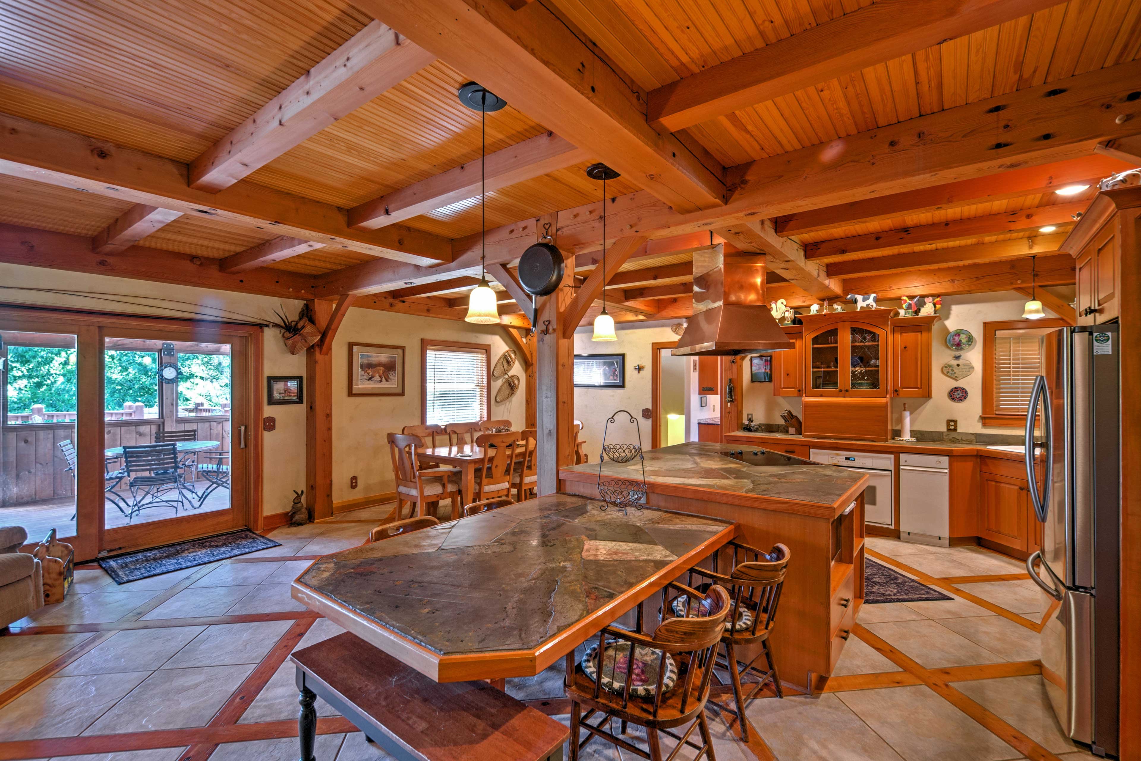 The kitchen features stainless steel appliances, a center island and paneling.