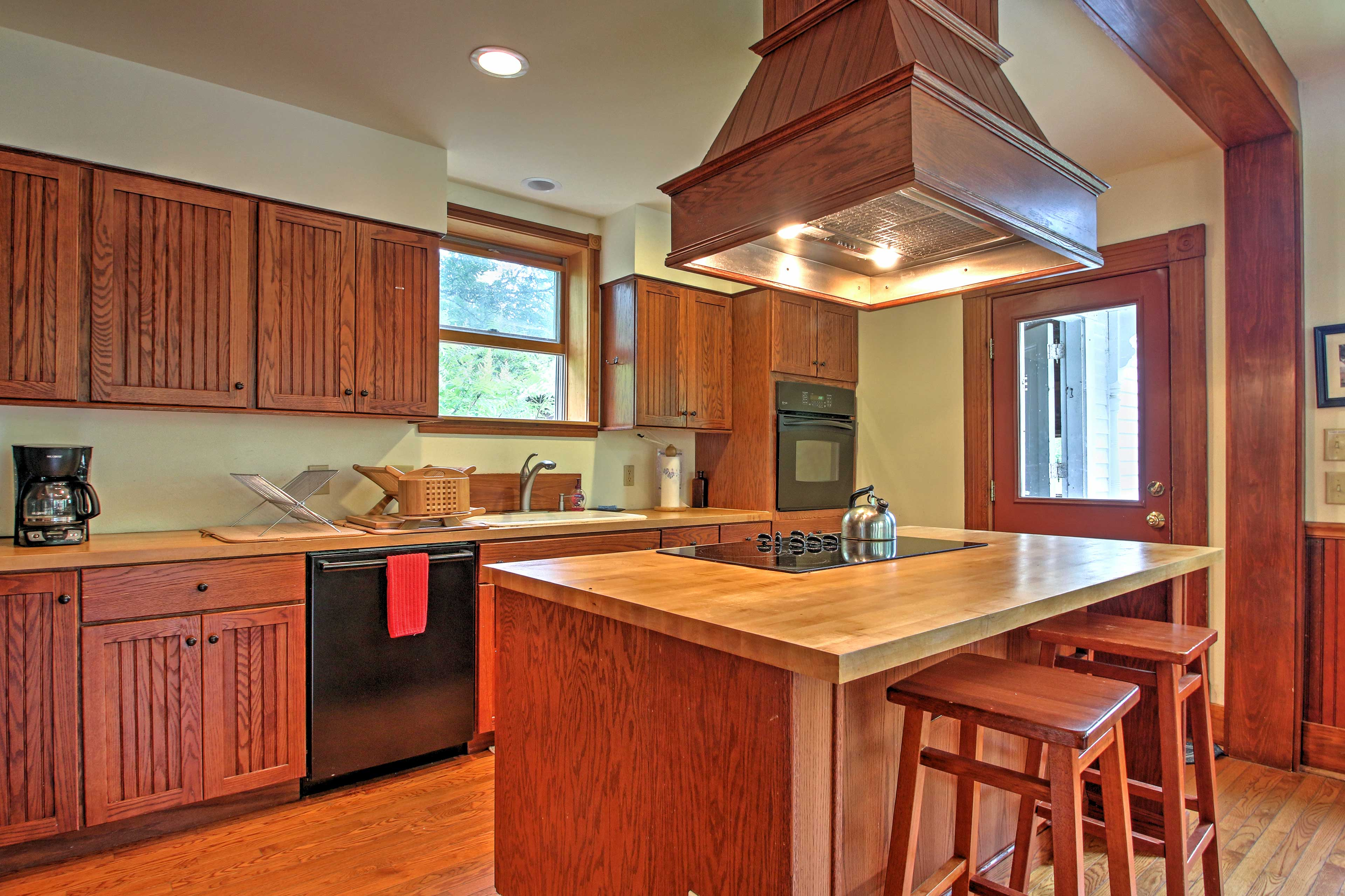 The kitchen is newly updated, featuring beautiful wood cabinets.