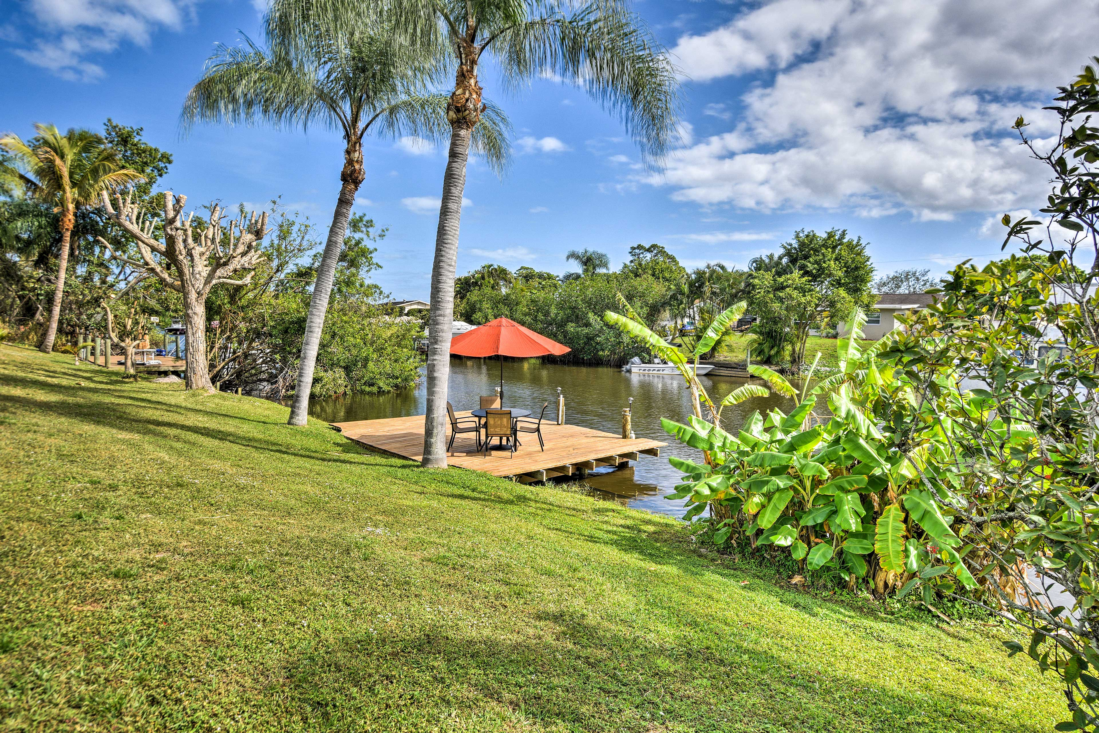 The large verdant green lawn leads down to the private dock!
