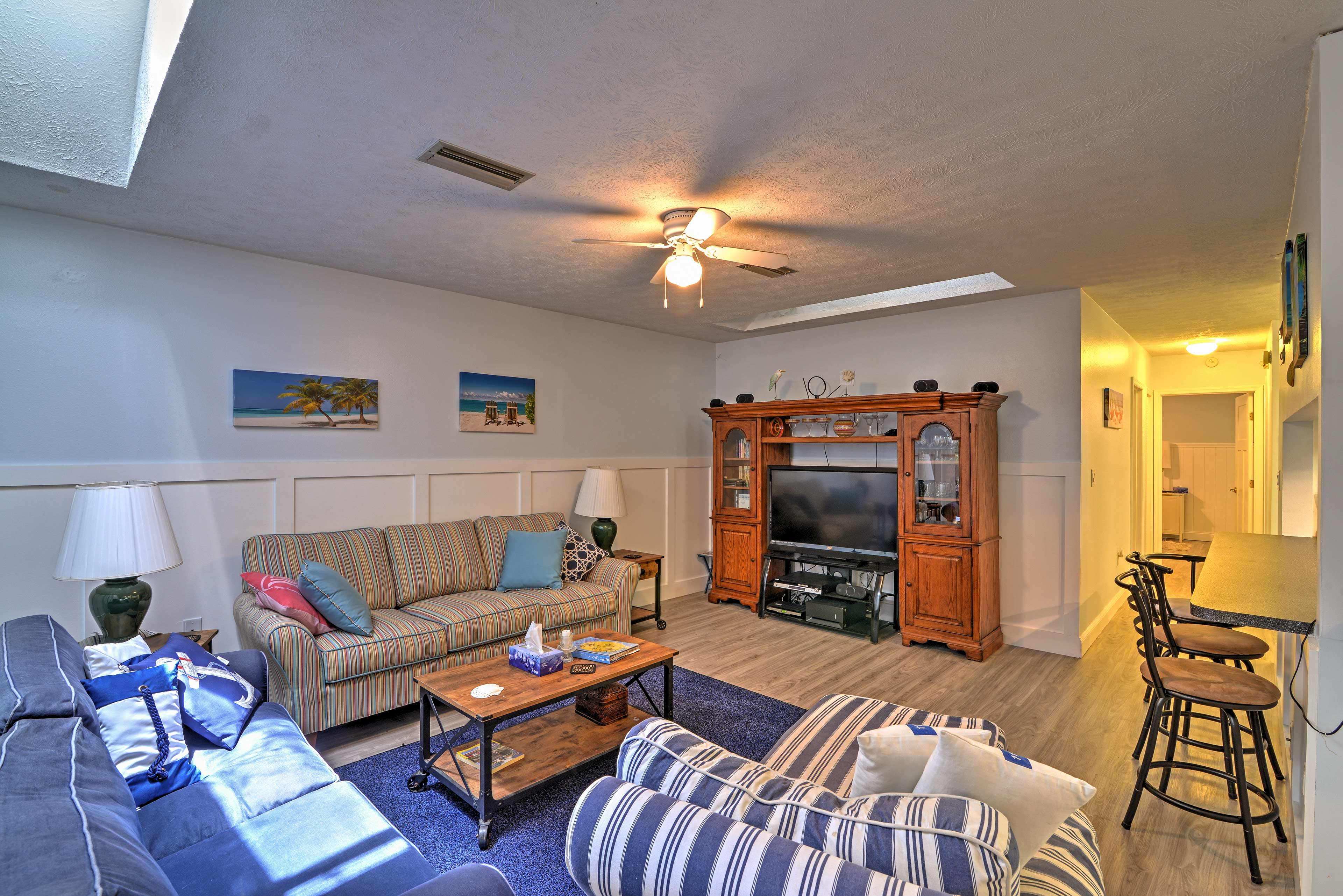 The living room offers couches, a chaise lounge chair & a flat-screen cable TV.