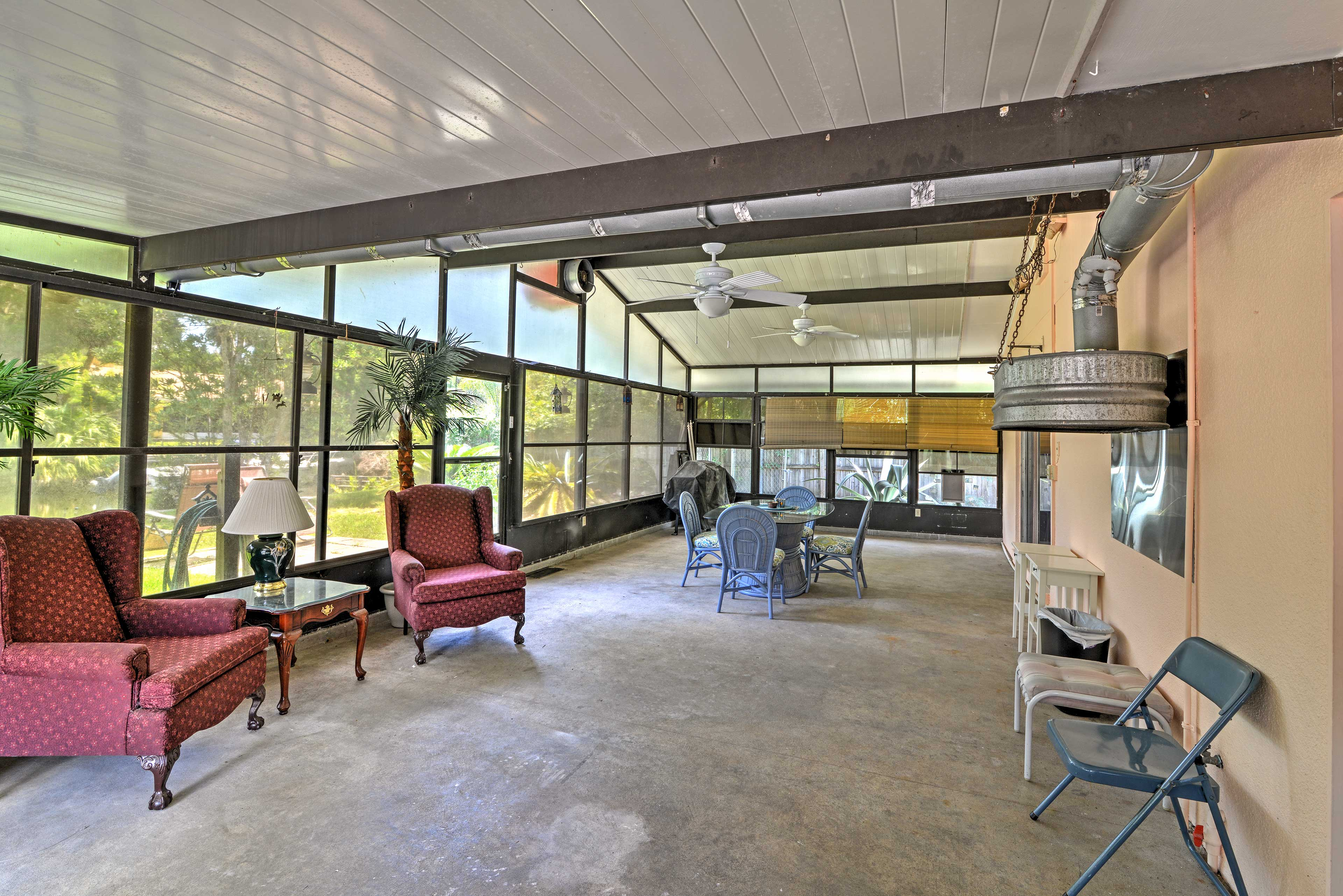 Walk out to the enormous screened in patio, which offers 2 armchairs & a table.