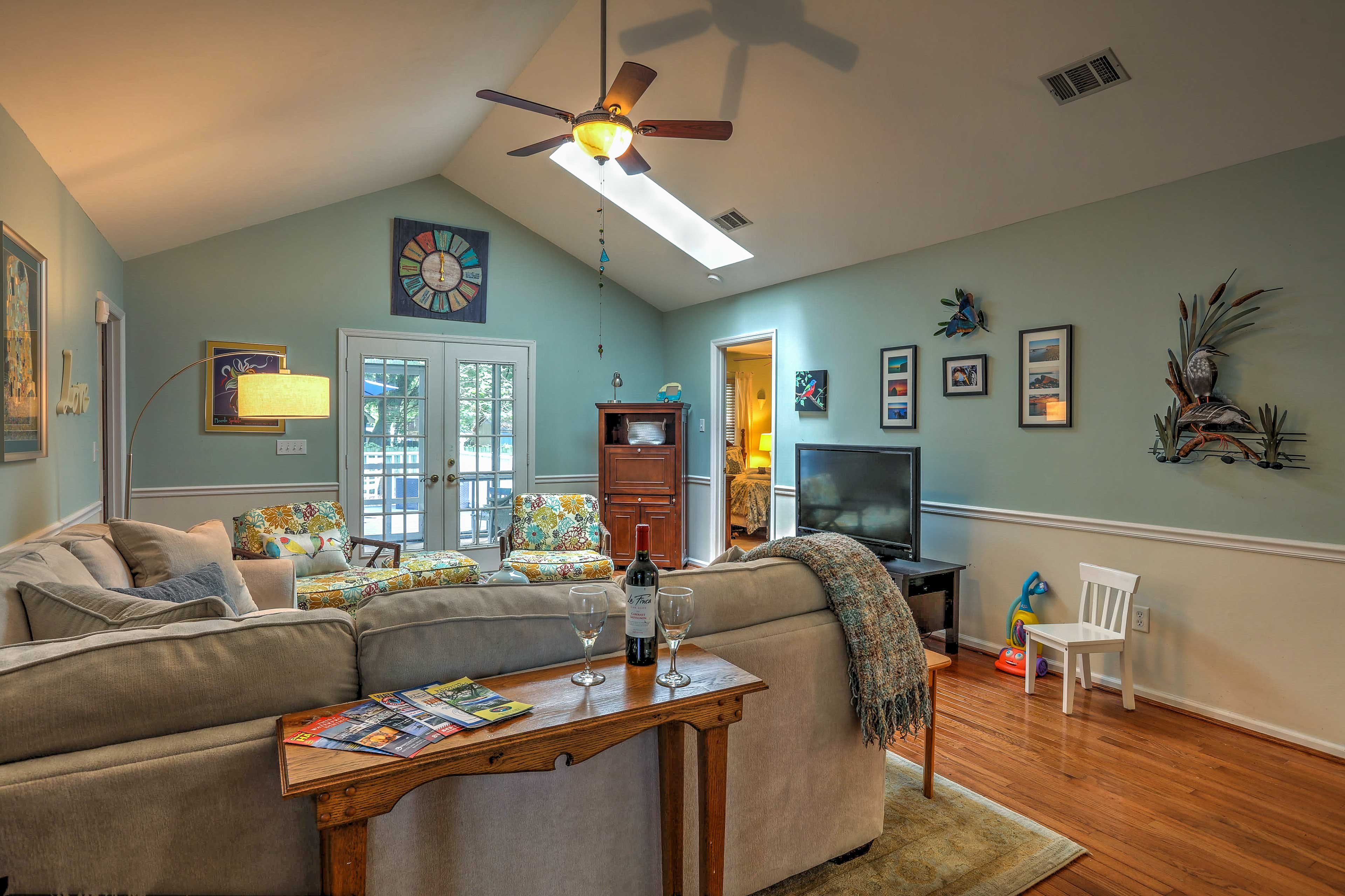 The living room features cool decor, a plush sectional & a flat-screen cable TV.