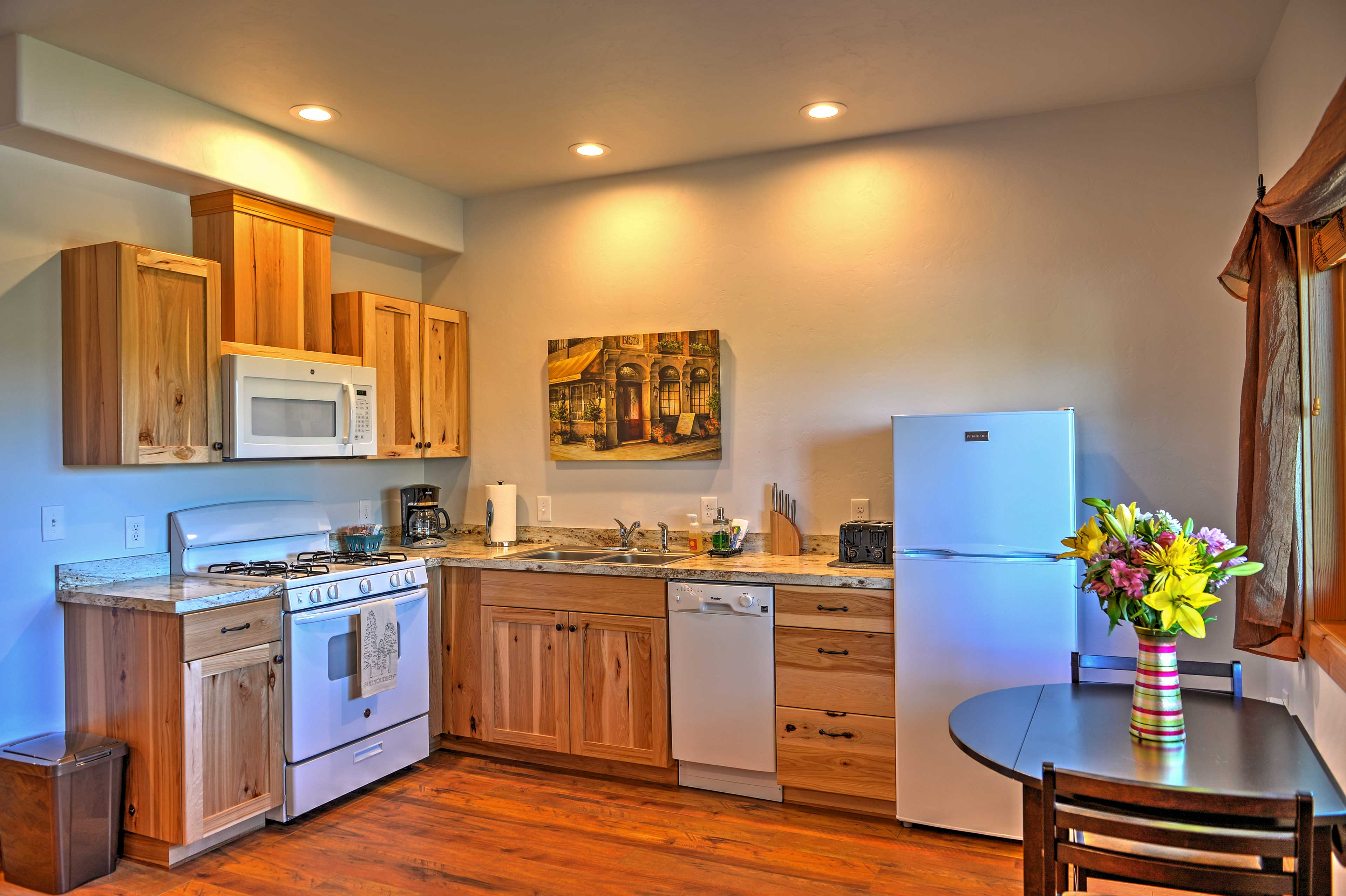 Sleek hardwood floors guide you through the fully equipped kitchen.