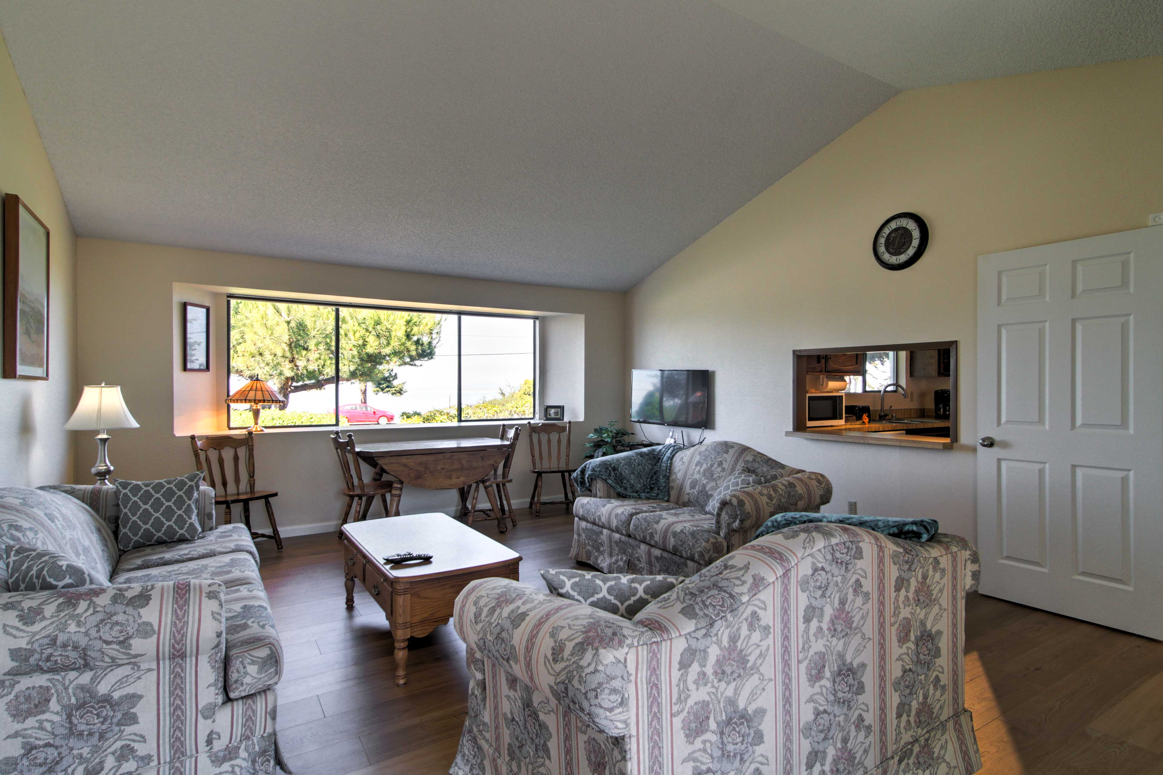 This living room has comfy furniture with a pass-through kitchen window.