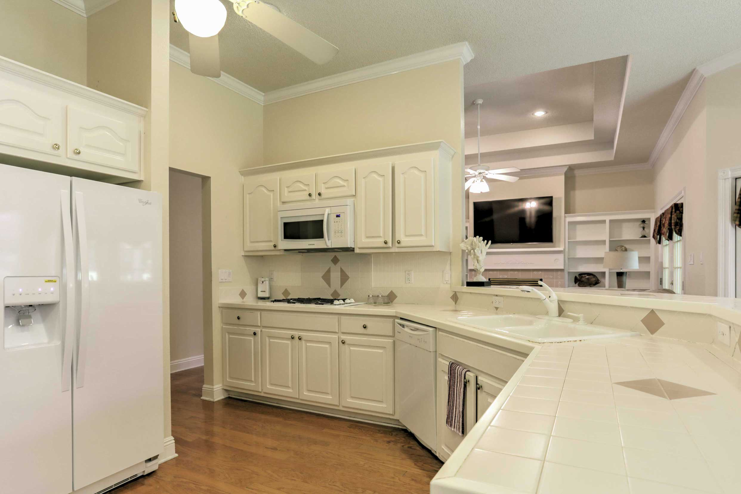 Utilize the sleek, white fully equipped kitchen to prepare home-cooked meals.