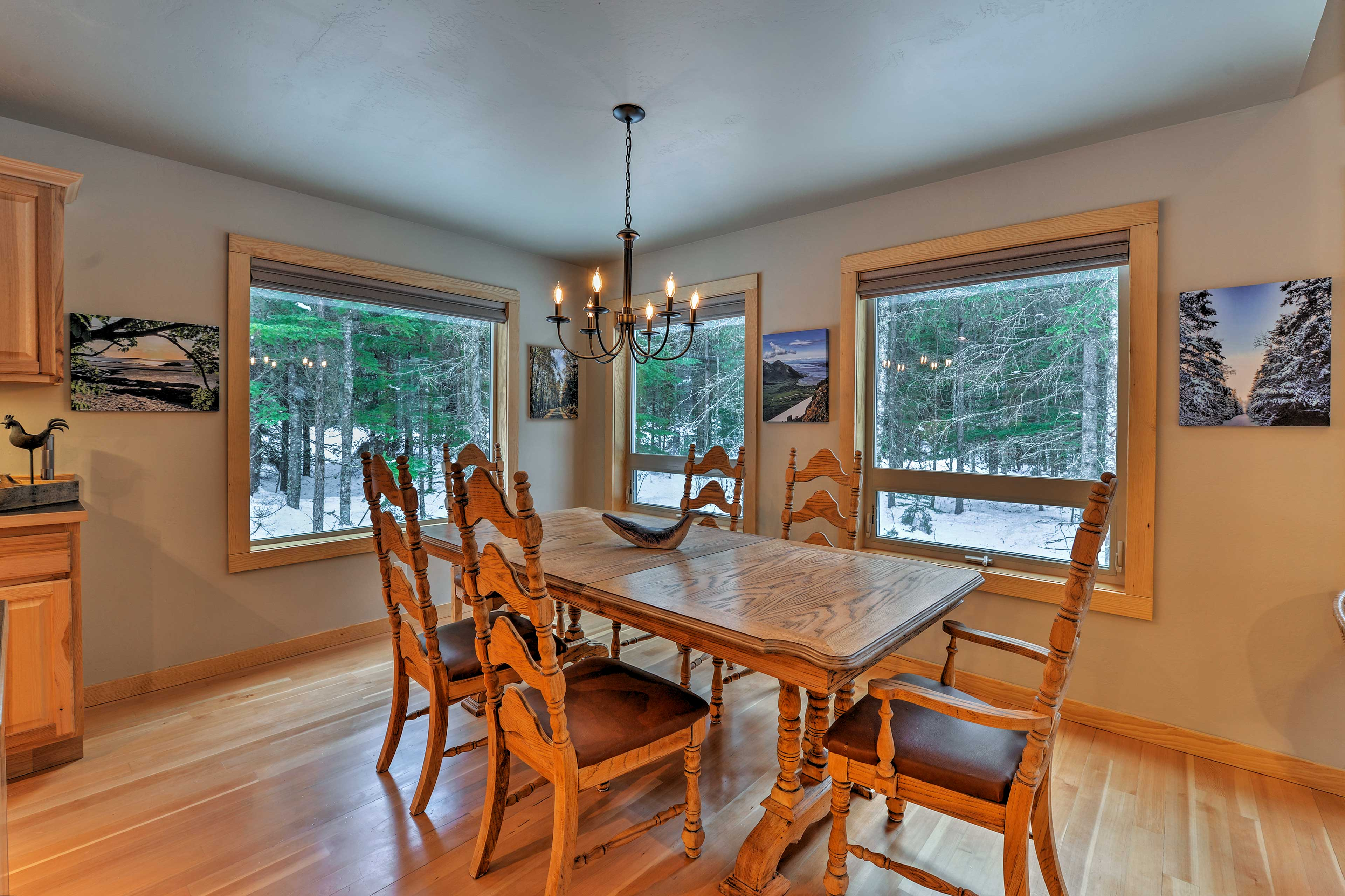 Enjoy dinner with a forest view at this dining table surrounded by windows.