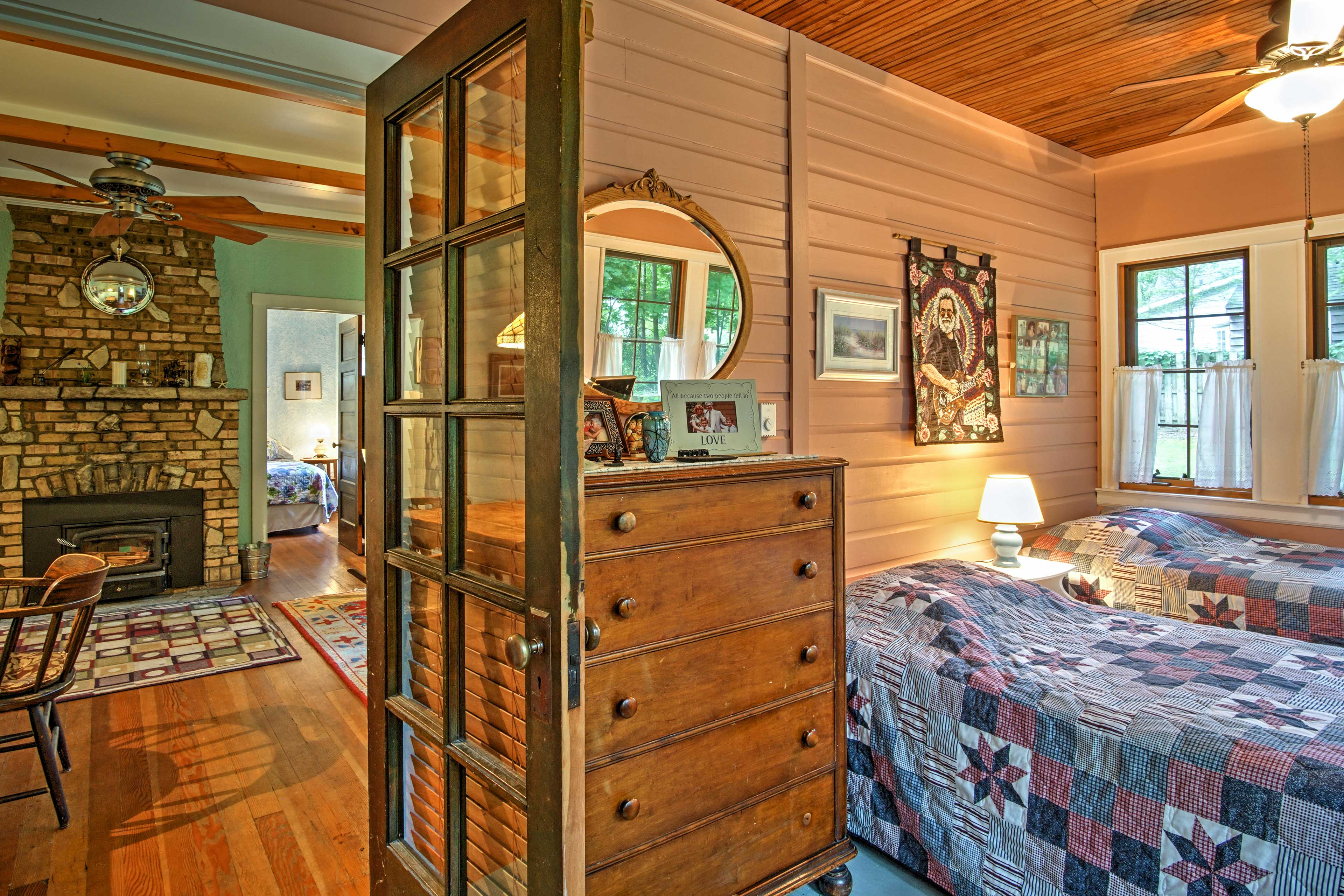 Just off of the living room is a cozy bedroom with wood paneling and charming windows.