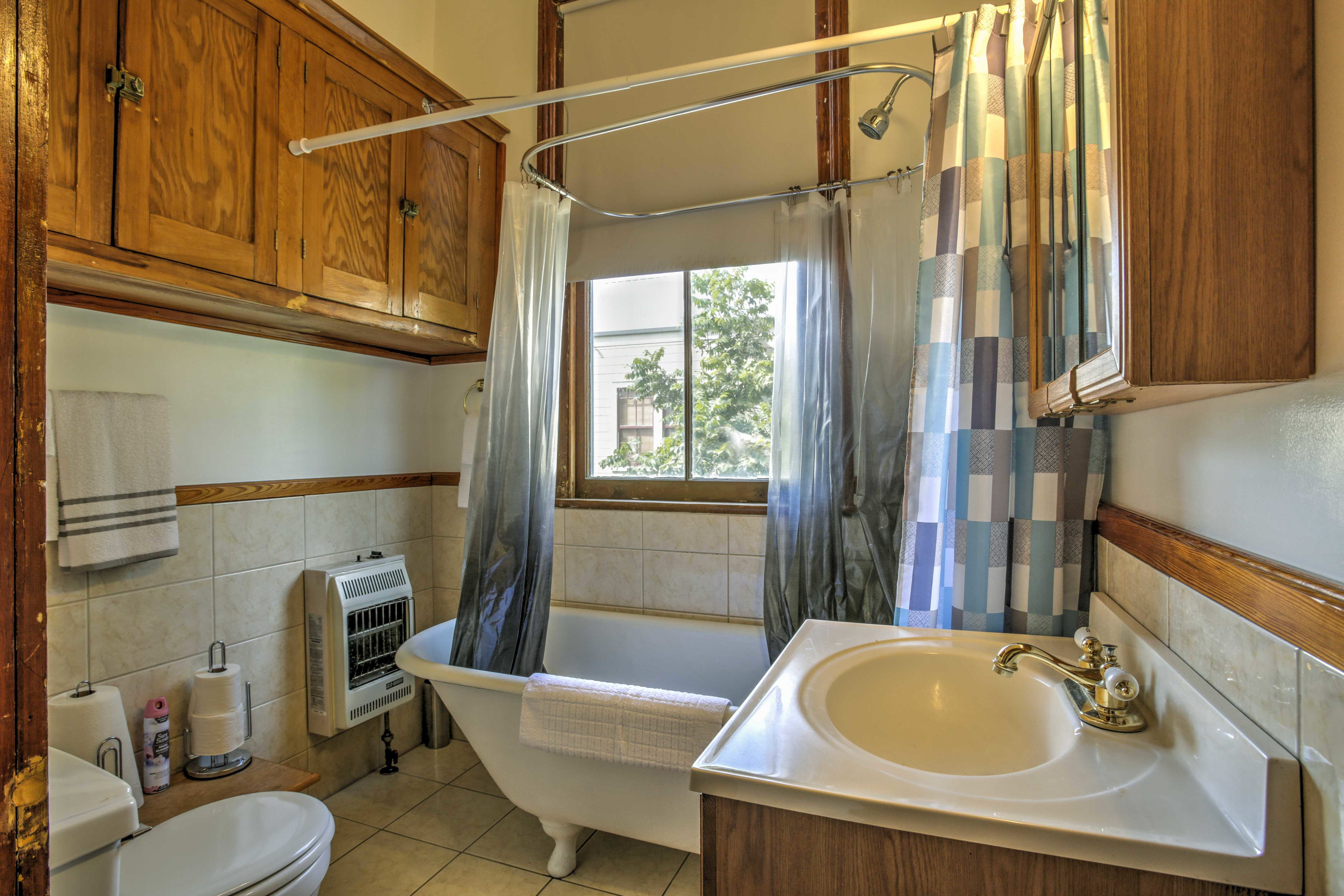 The bathroom features a clawfoot tub that has been modified with a showerhead.