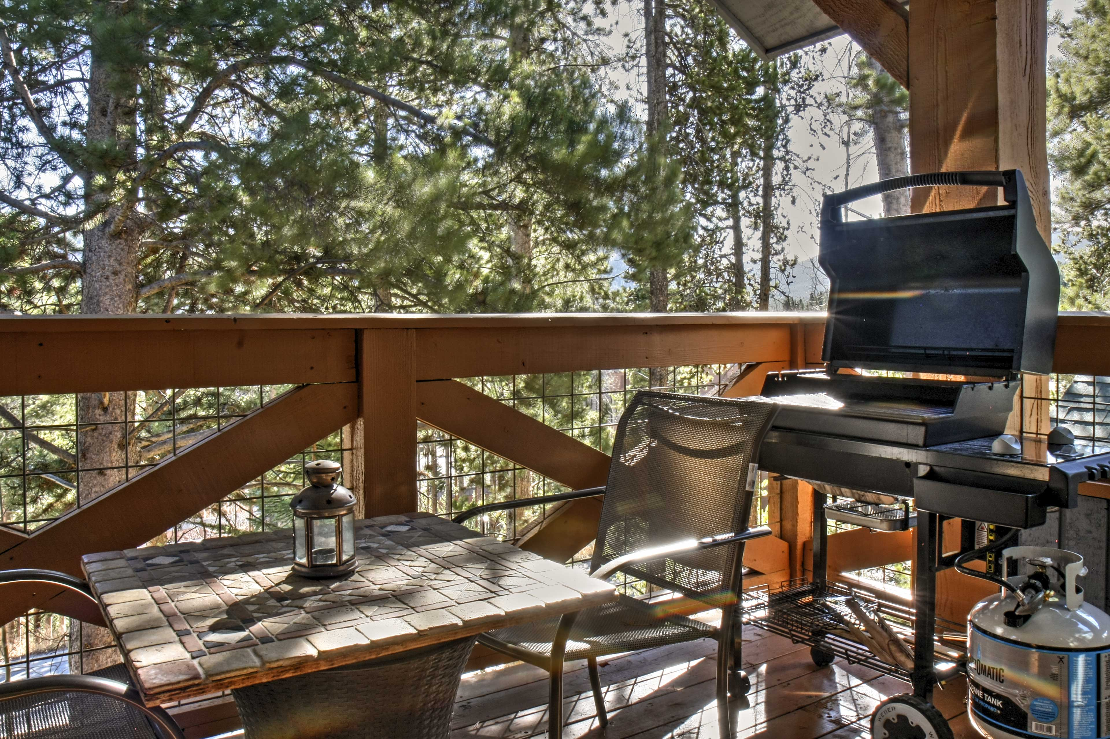 Head outside to the deck featuring a gas grill and seating surrounded by pines.