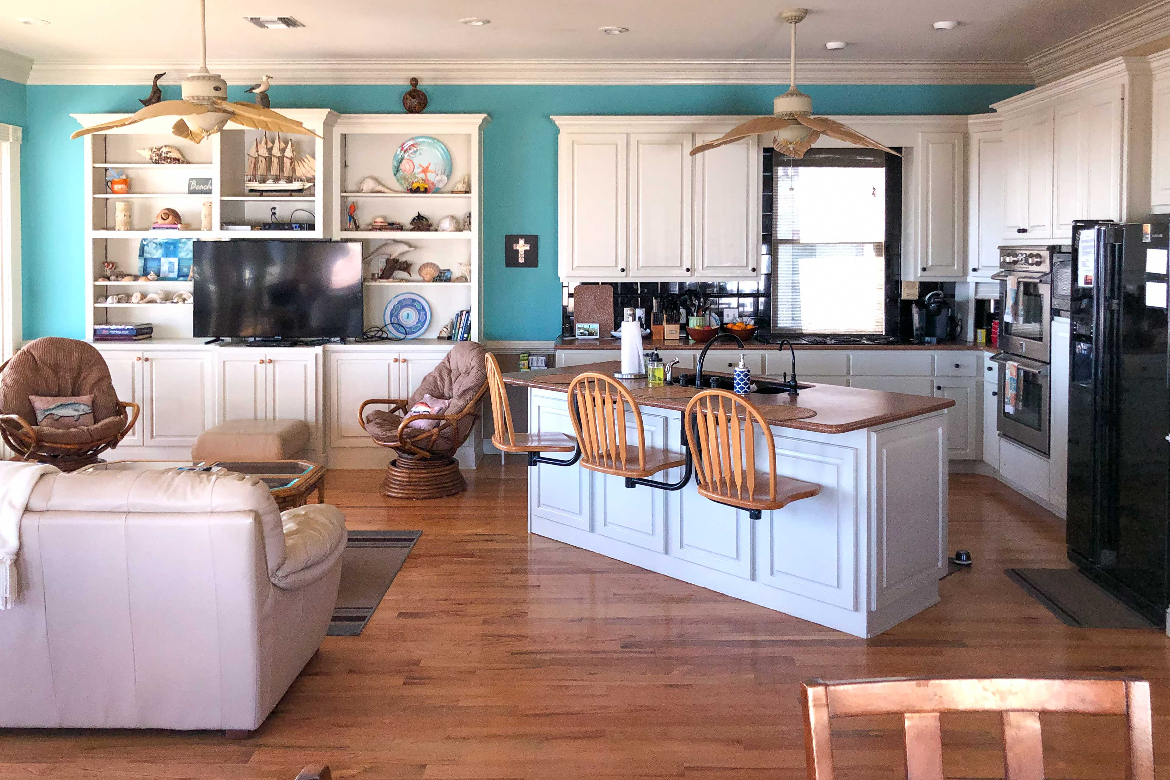 The first fully equipped kitchen offers an island w/old-fashioned swivel chairs.