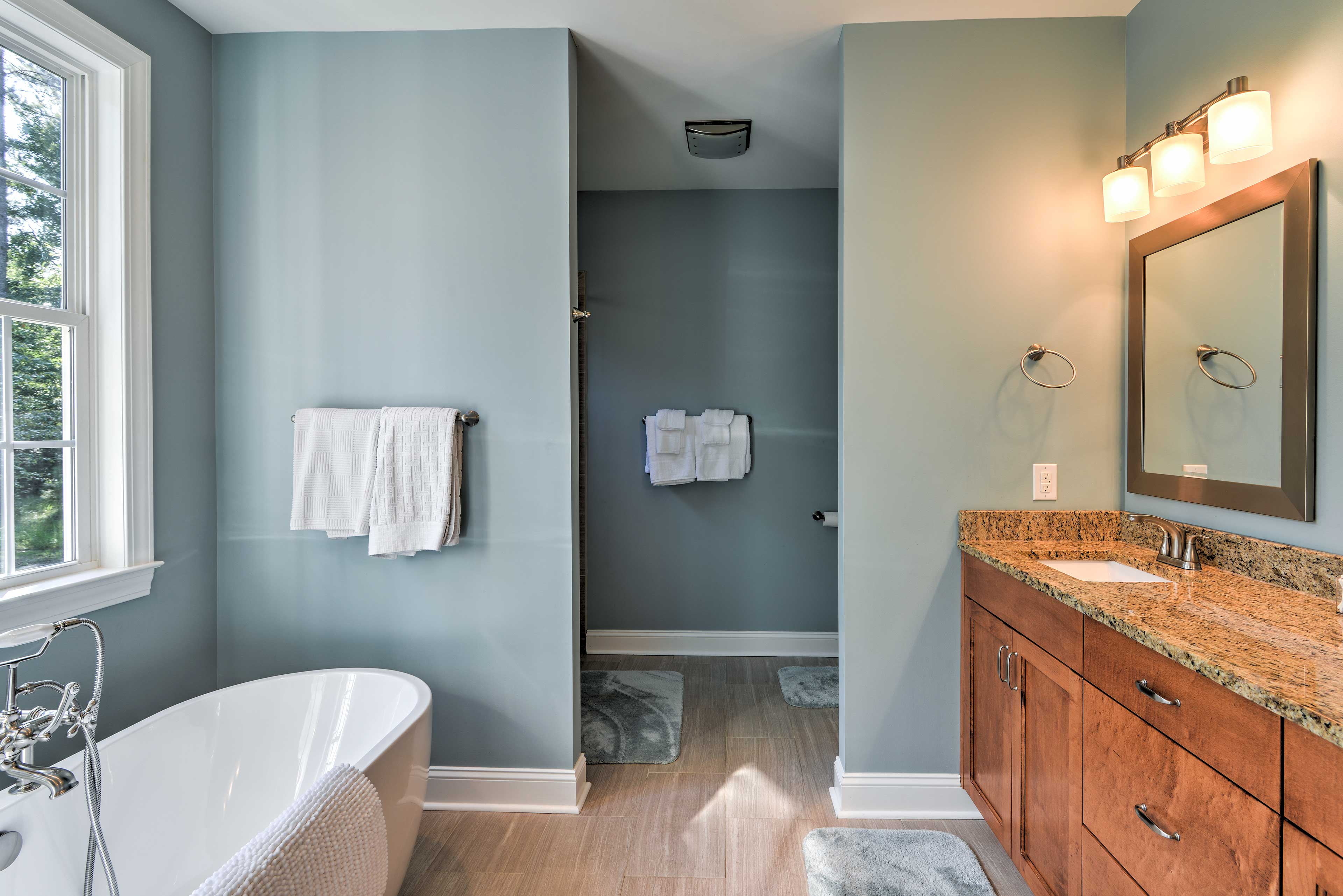This bathroom is complete with a clawfoot tub, walk-in shower, and granite vanity counters.